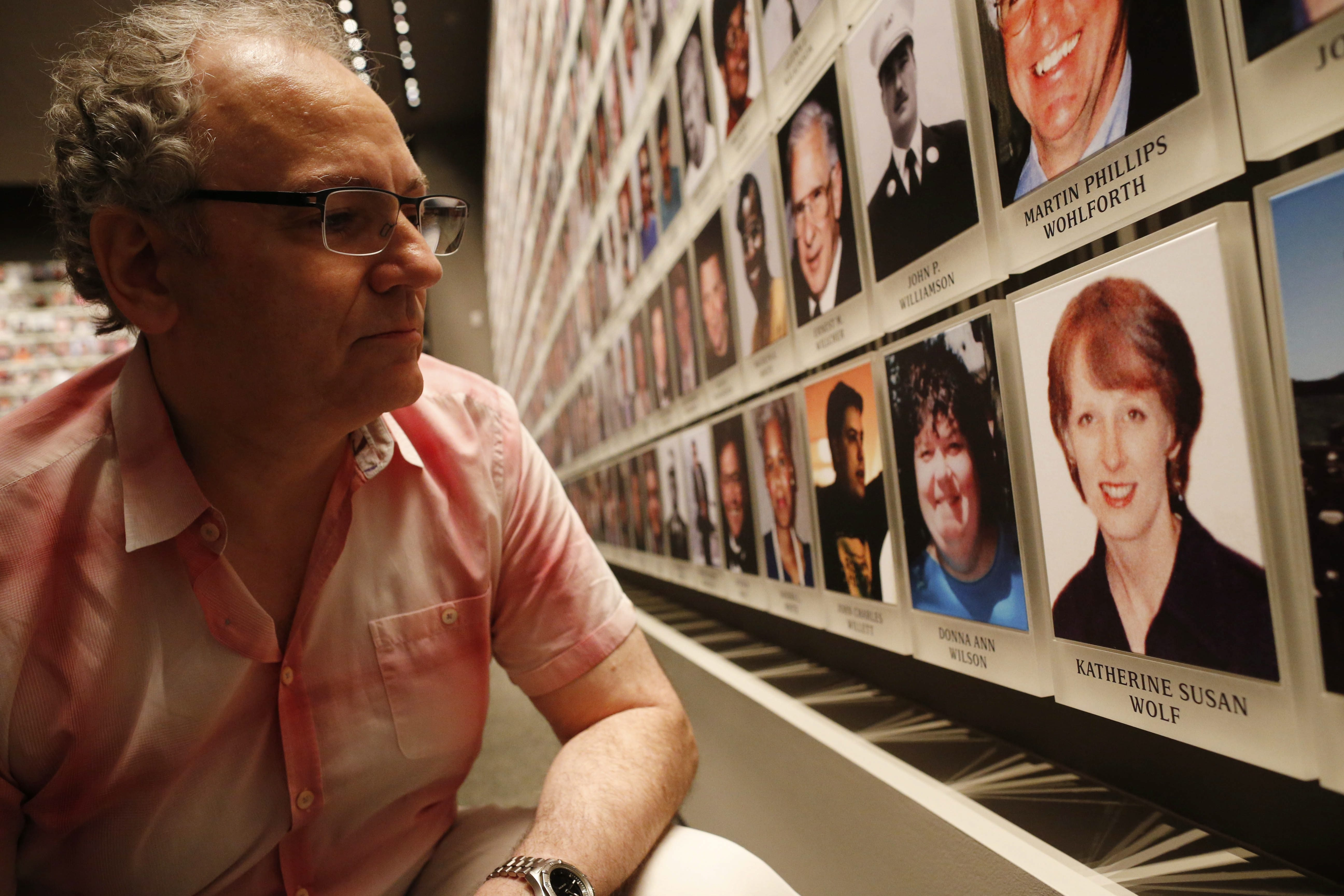 Charles Wolf, whose wife, Katherine, was killed in the 9/11 terrorist attacks on the World Trade Center, looks at his wife's photograph on the 'Wall of Faces' in the Memorial Exhibition at the National September 11 Memorial and Museum in New York City, Tuesday, Aug. 25, 2015.  (Derek Gee/Buffalo News)
