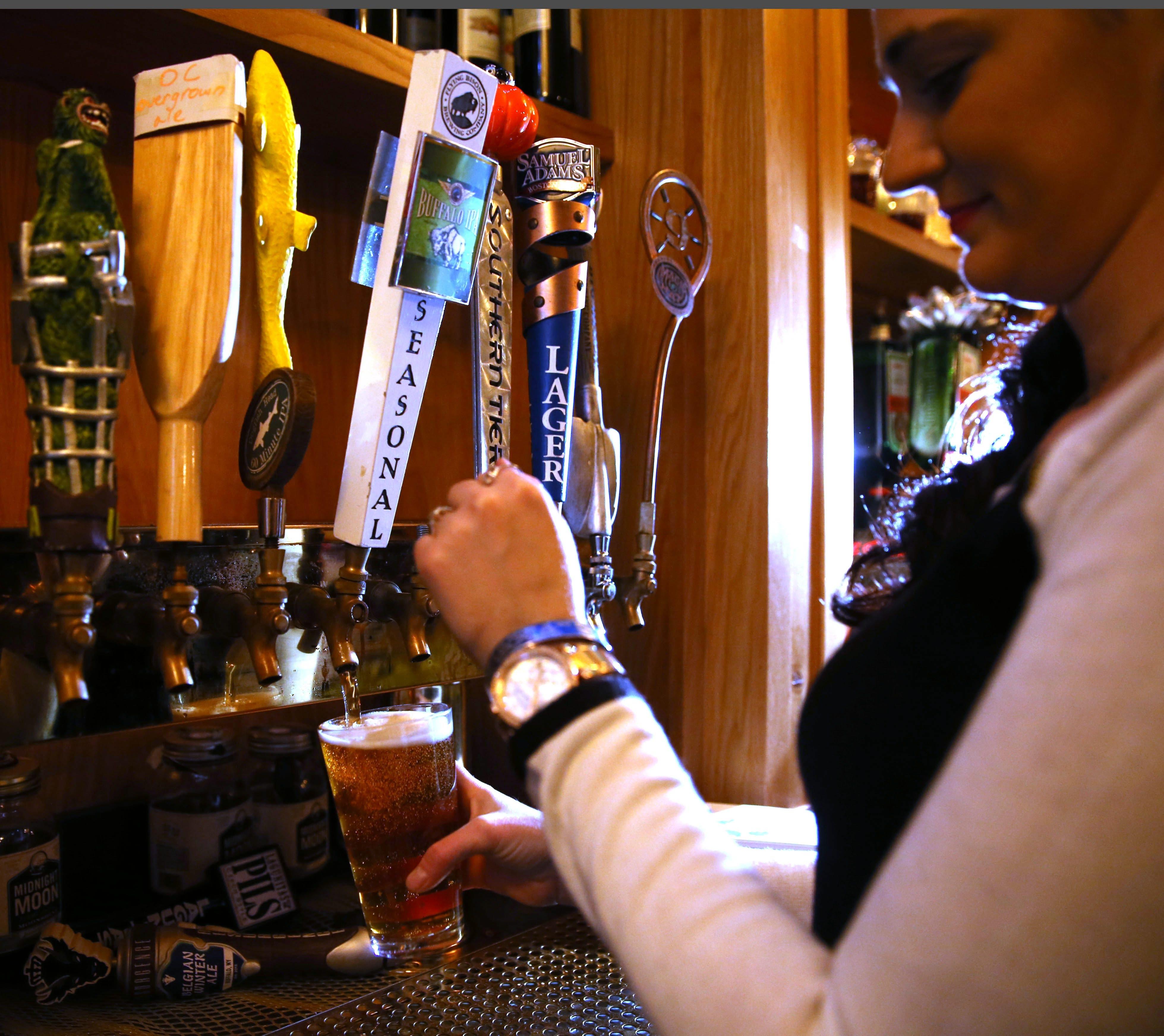 Bartender Allison Keane pours Flying Bison at the Armor Inn Tap Room, 5381 Abbott Road, Hamburg.