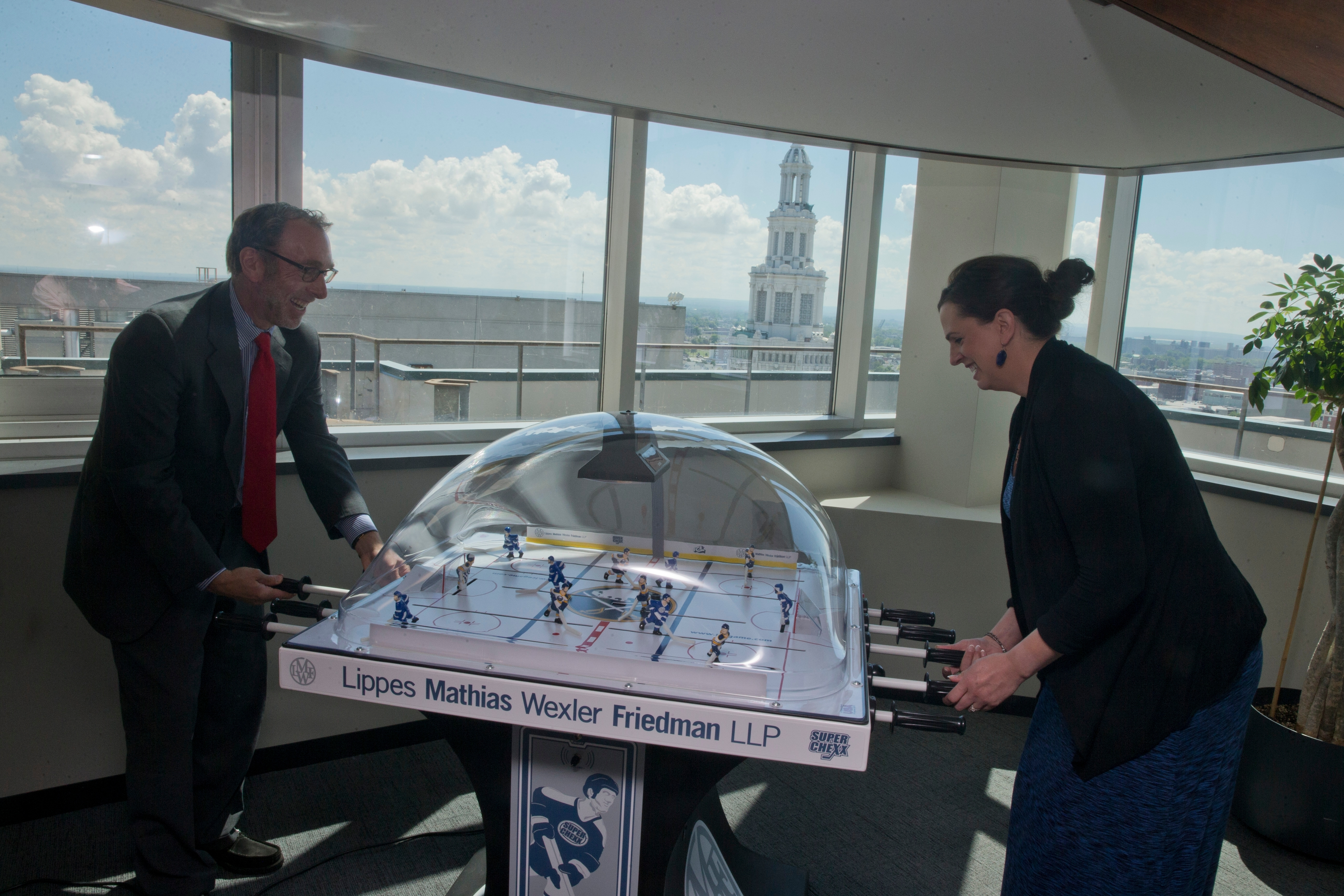 """""""The work I do is what can be done to reinforce trust, to focus on culture, to focus on clear principles and principle-based decisions. To focus on communications guidelines."""" – Scott E. Friedman, chairman and CEO of Lippes Mathias Wexler Friedman, here playing bubble hockey with Colleen K. Mattrey, a partner in the law firm, at the Fountain Plaza offices downtown"""