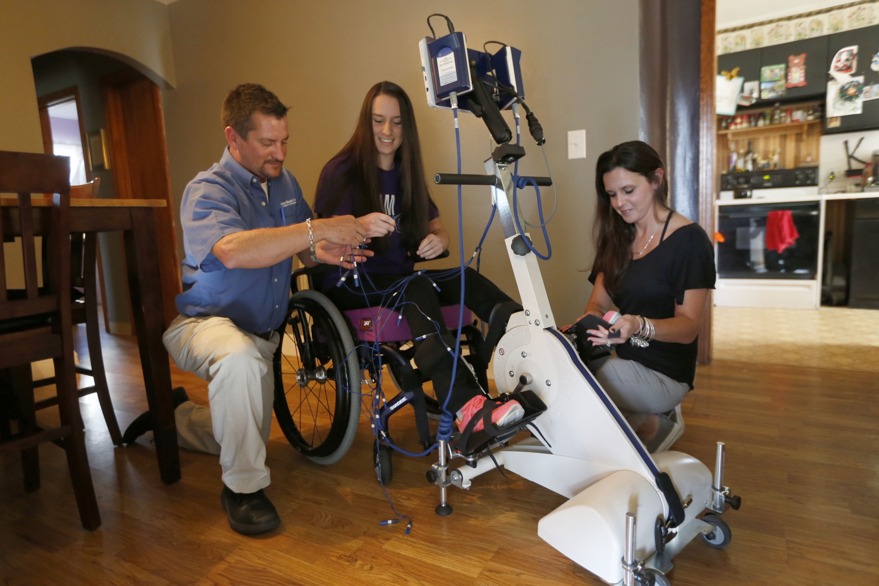 From left, Dad Chris Kern, Ashley, 17, with her RT300 Functional Electrical Stimulation Bike, and Mom Jill at their Cheektowaga home on Friday, Sept. 16, 2016.  (Robert Kirkham/Buffalo News)