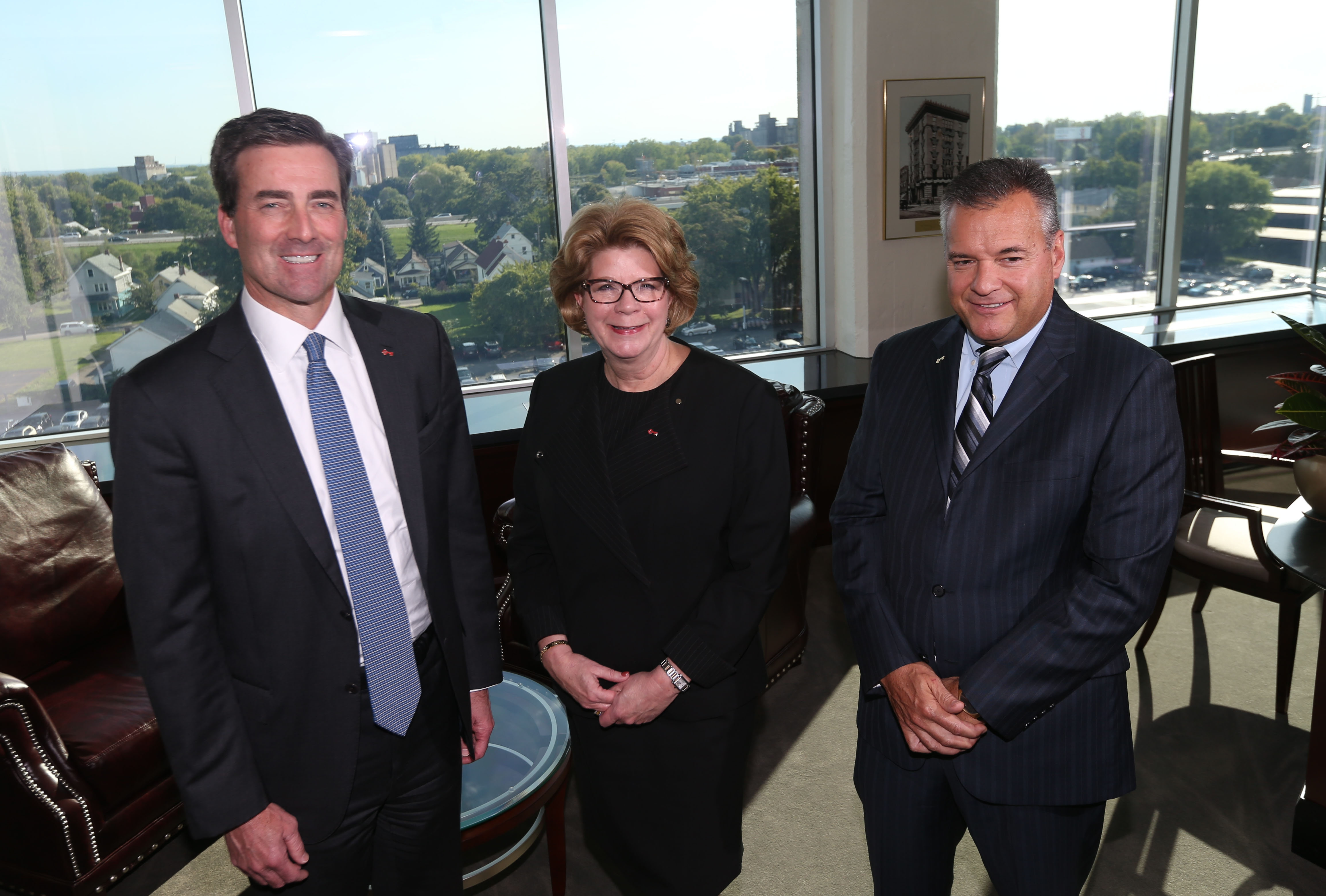 """KeyCorp management team – from left, Christopher M. Gorman, merger-integration executive; Beth E. Mooney, chairwoman and CEO; and Gary D. Quenneville, upstate regional chief – gather at Larkinville to strategize on First Niagara conversion.  """"When your credit card expires and it's time to replace, that's when you get your KeyBank credit card. We're trying to do this in a way where you don't have to change because we changed."""" Beth E. Mooney, Key chief executive"""