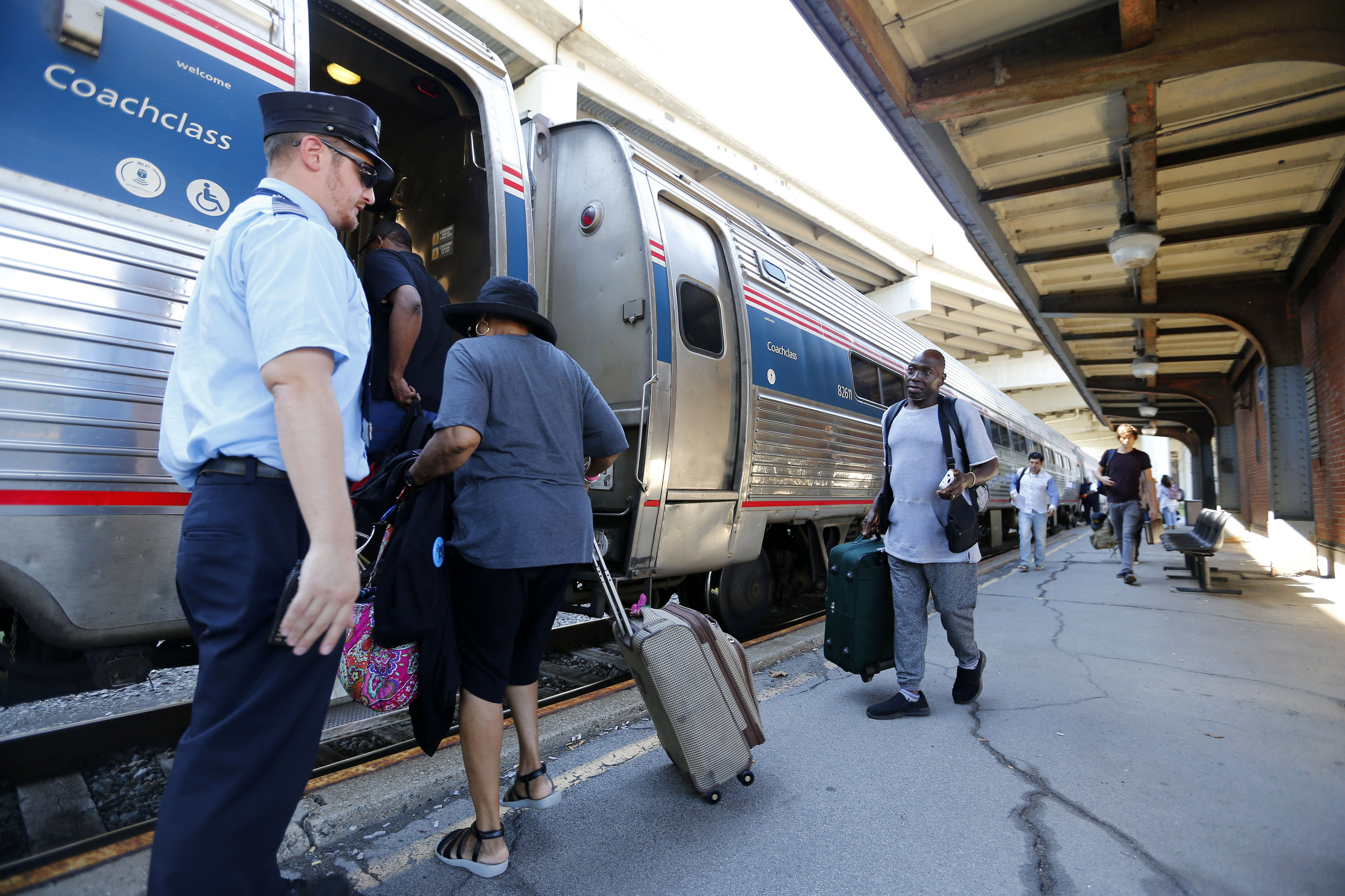 Passengers juggle their luggage as they board an Amtrak train at the passenger railroad station on Exchange Street in Downtown Buffalo. The station is overdue for a modernization upgrade.