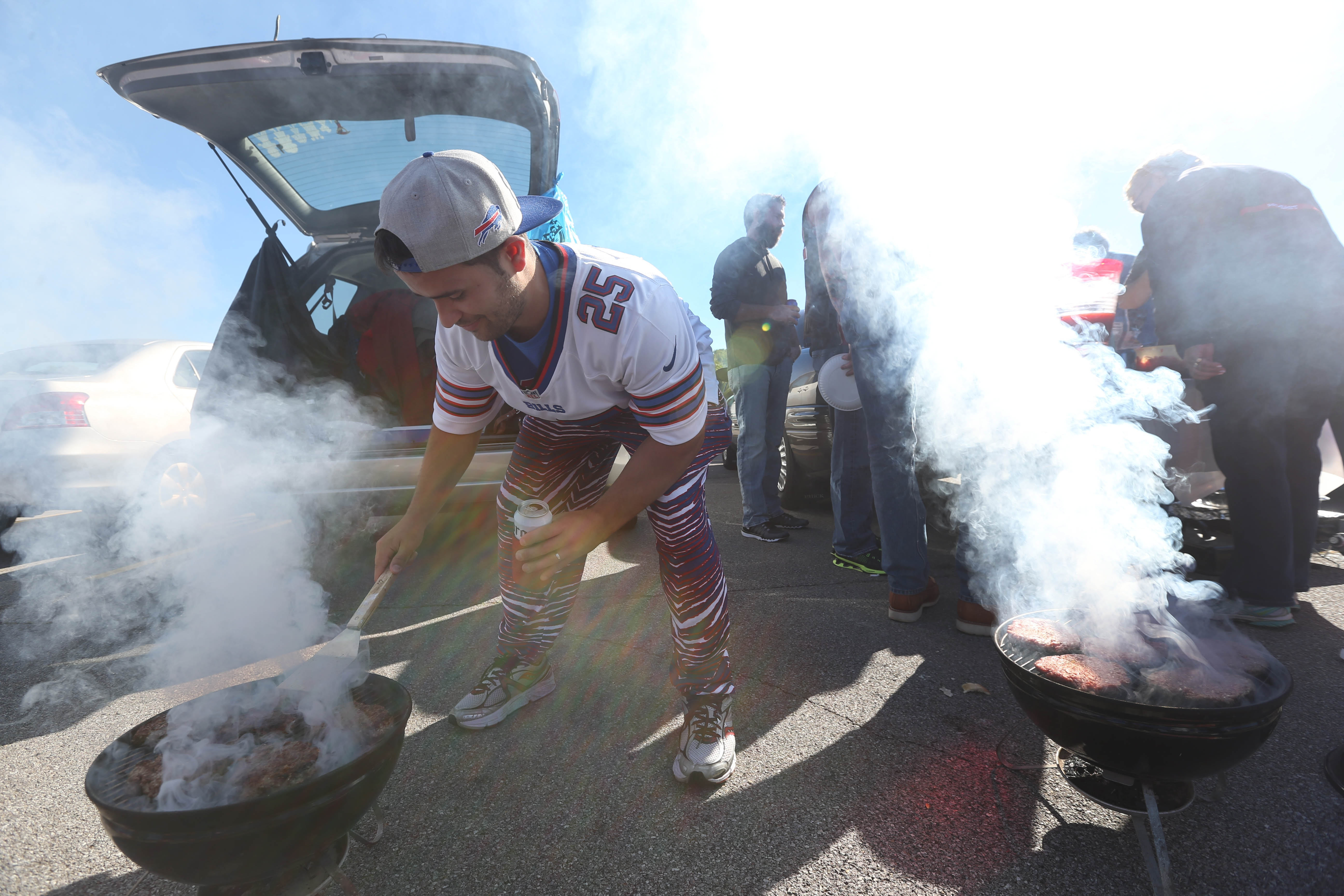 Tailgating tradition: Scenes from last week's festivities include 14-year-old Jacob Lawson and his funky hat, Jeff Manca working two grills, Petey Robinson with hot eats just out of the smoker, and Lori Pafk heating up a big pot of chili.
