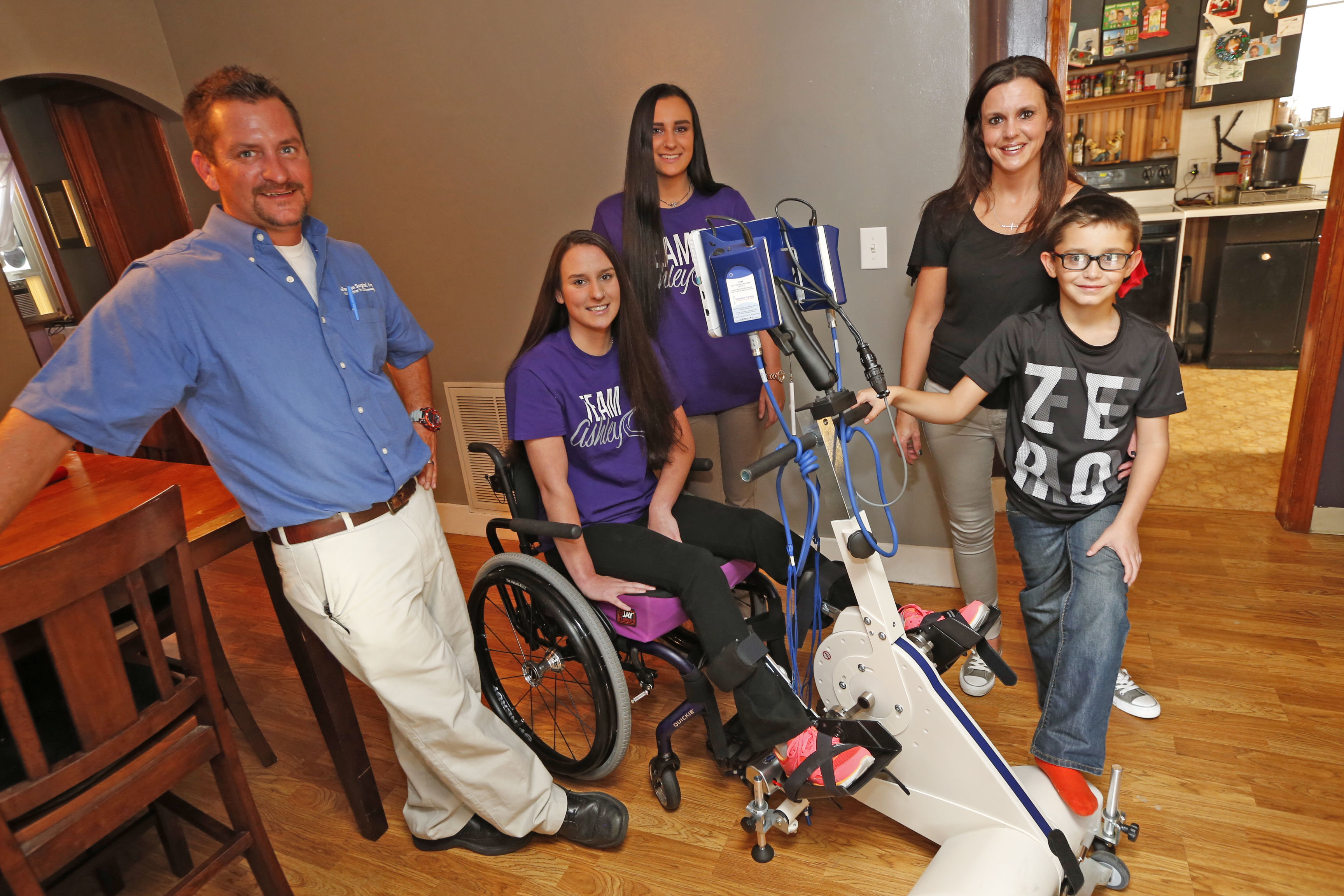 Ashley Kern is seen on an electrical stimulation bike with dad Chris Kern, twin sister Alex, 17,  mom Jill and little brother Christopher, 9, at their Cheektowaga home.  (Robert Kirkham/Buffalo News)