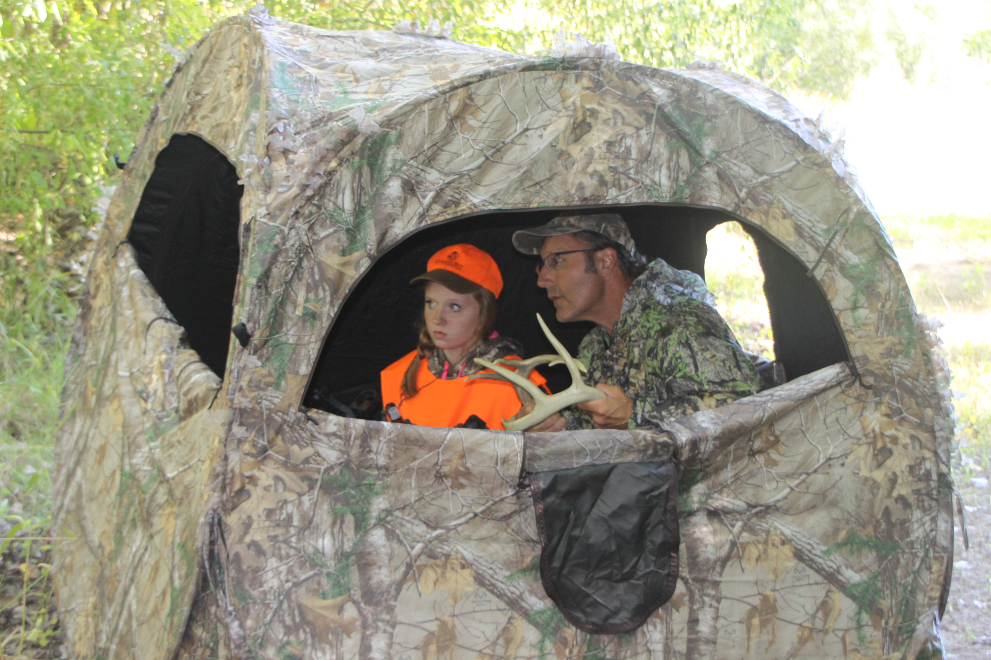 Arnie Jonathan of Lockport shows Emily Eaton of Newfane how to try and call a deer into range from their portable blind.