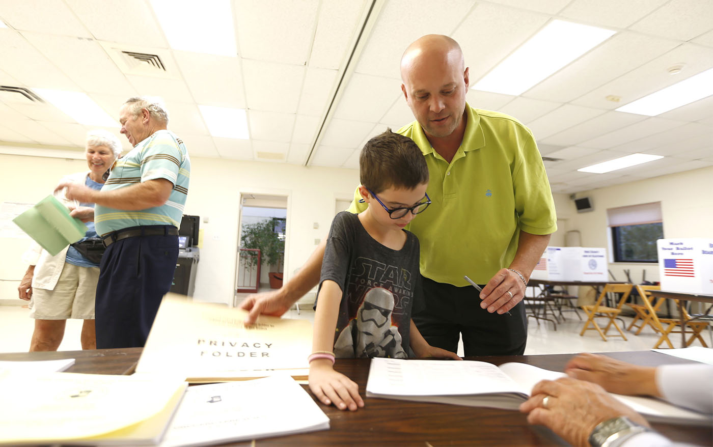 Pictures, Scott Kroll of Orchard Park shows his son Max, 8, how the voting process works at his neighborhood polling place at Nativity of Our Lord school in Orchard Park on Tuesday, Sept. 13, 2016. (Robert Kirkham/Buffalo News)