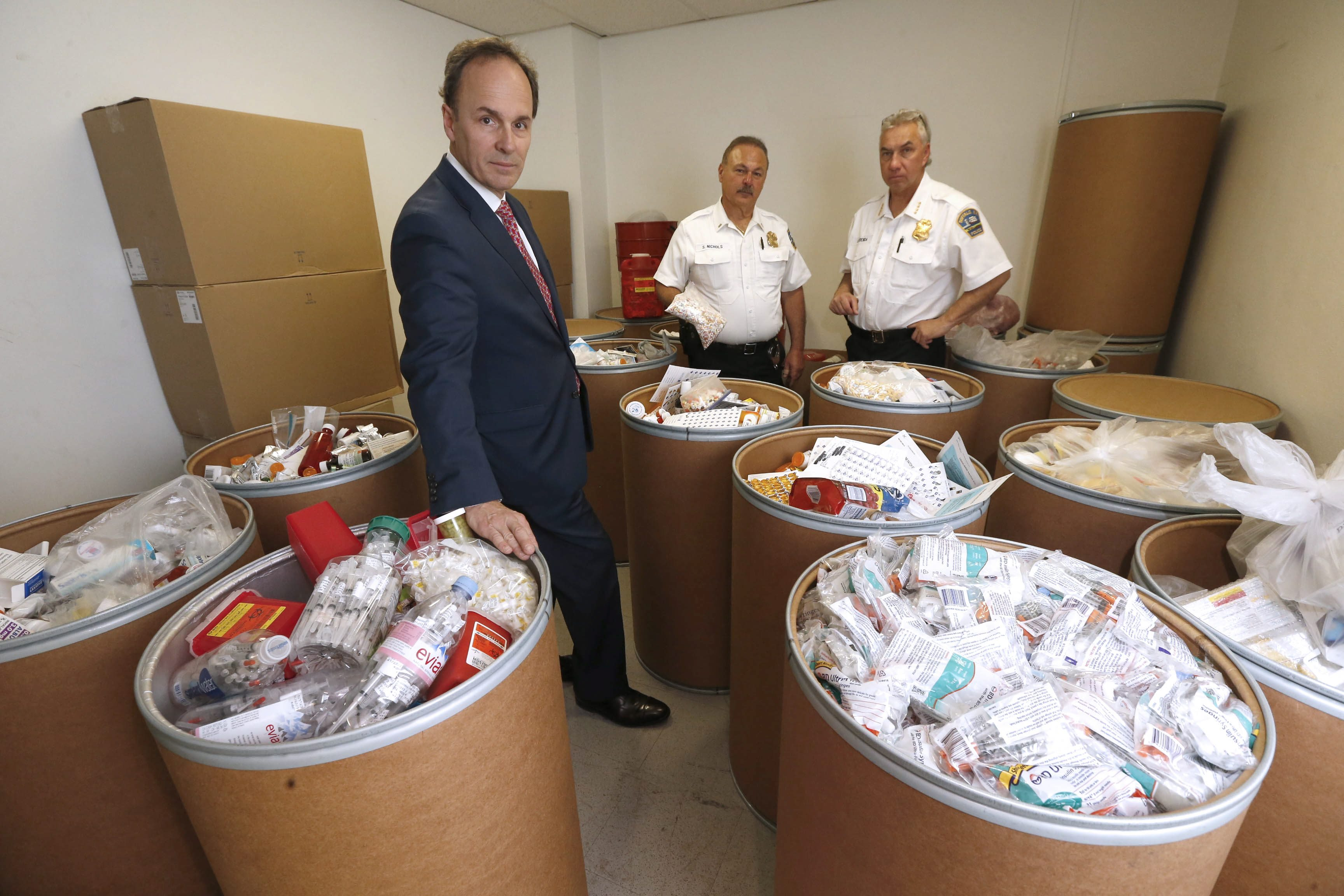 From left, U.S. Attorney William Hochul, Lt. Steven J. Nichols and Buffalo Police Commissioner Daniel Deranda survey the 18 55-gallon drums of drugs and needles that have been turned over at drop-offs at the BPD's five district stations on Friday, April 29, 2016. (Robert Kirkham/Buffalo News)