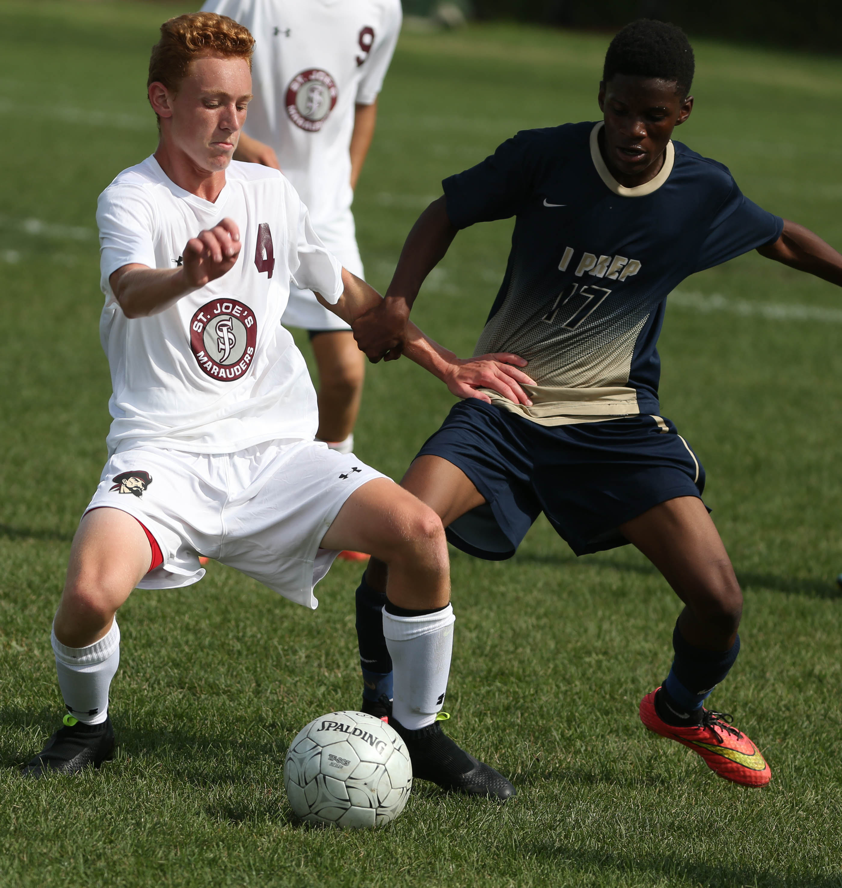 St. Joe's Mitchell Kubiak battles International Prep's Abdikarium Sabtow in the second half of a game on Aug. 31. The Marauders and Presidents are among the top teams voted into this week's soccer polls.  (James P. McCoy/ Buffalo News)