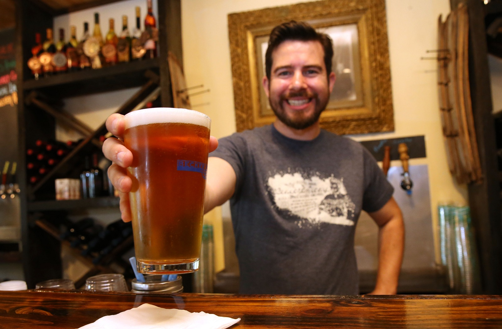 Winemaker Andres Vizcarra fills in as bartender at Becker Brewing and serves up the Local Lager, one of their favorite brews. (Sharon Cantillon/Buffalo News)