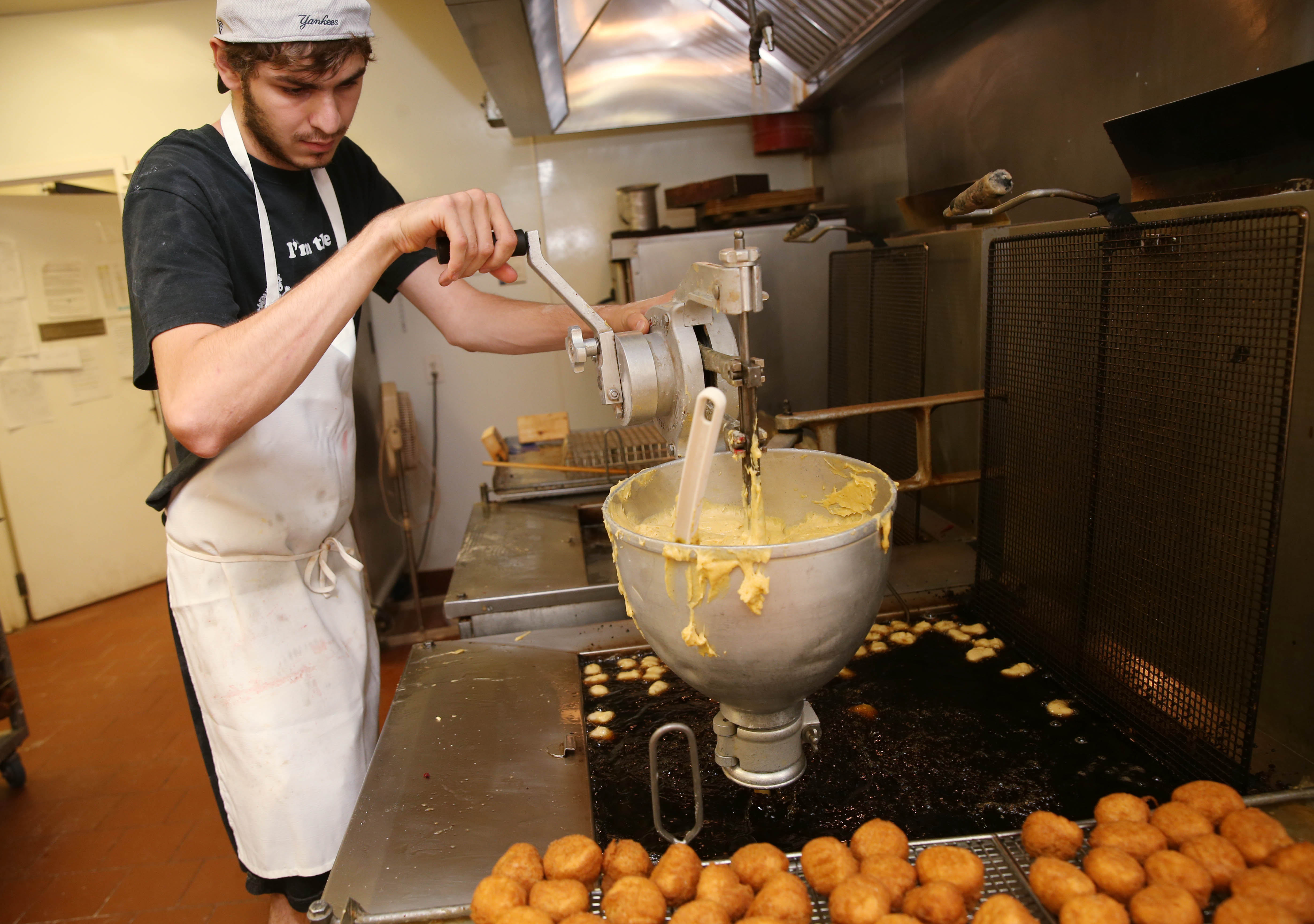 David Calleri uses the hopper to drop four doughnut holes into the oil at a time. (Sharon Cantillon/Buffalo News)