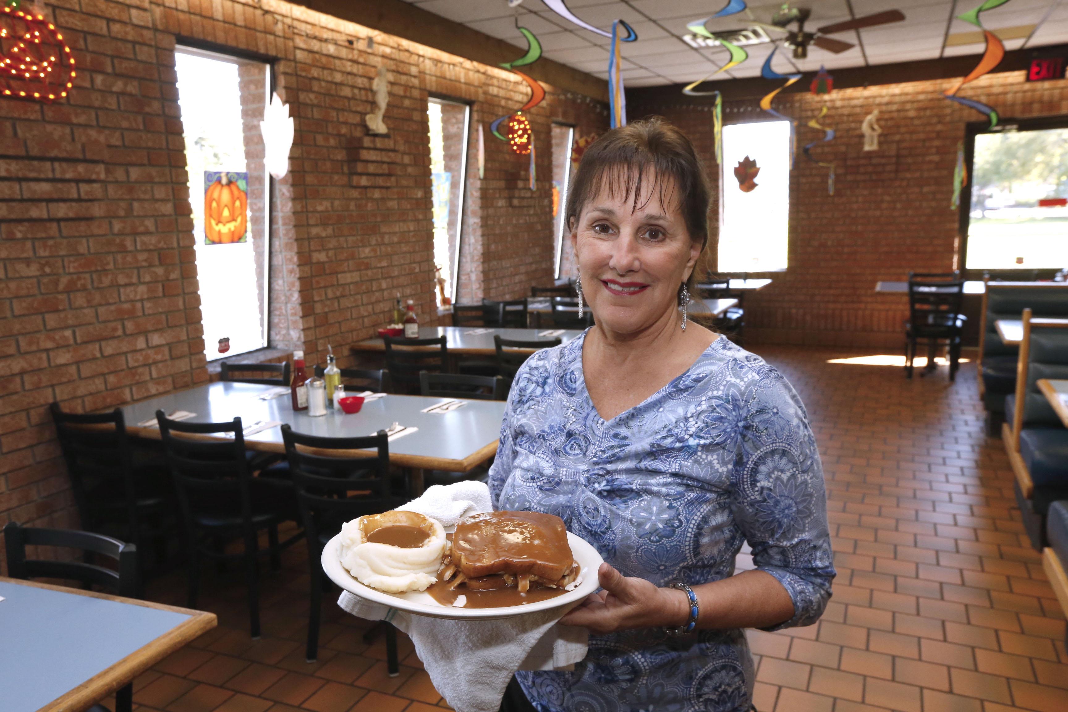 Head server Rose Matyjasik serves the open face fresh turkey sandwich, gravy and mashed potatoes at the  Seneca Towne restaurant.   (Robert Kirkham/Buffalo News)