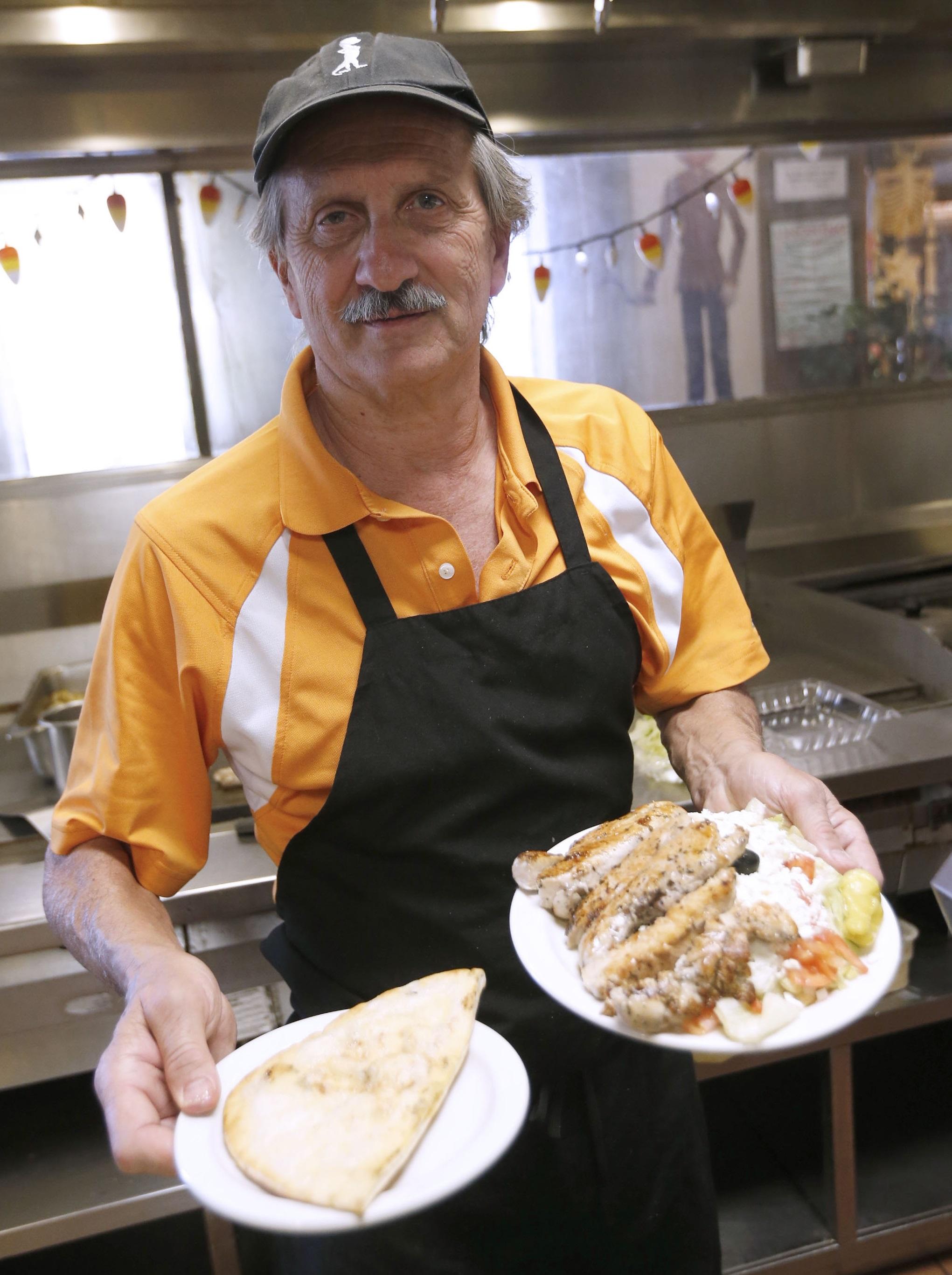 Owner Steve Triantafillou shows off the signature Greek chicken souvlaki at the Seneca Towne restaurant in West Seneca. (Robert Kirkham/Buffalo News)