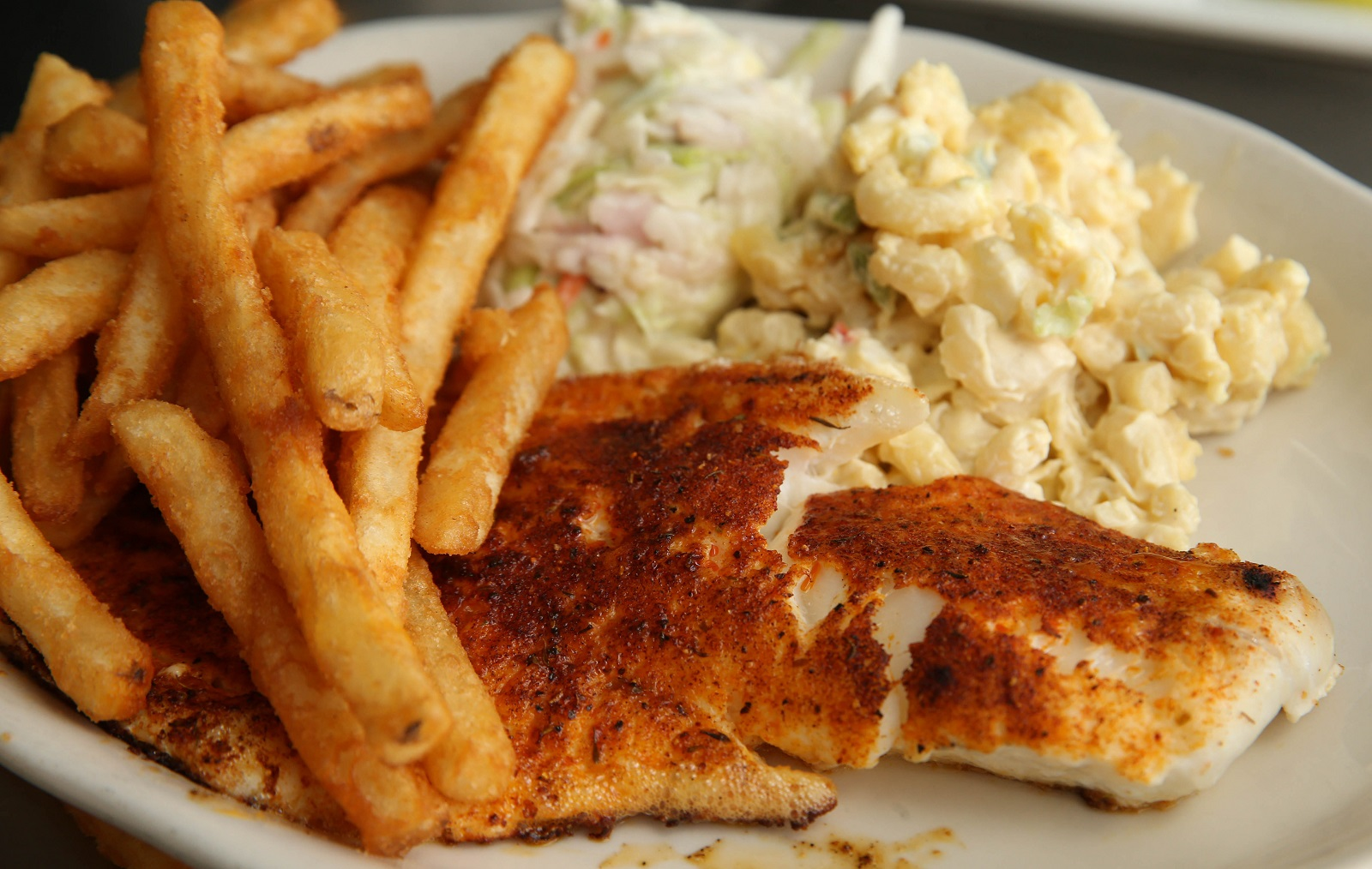 The Cajun broiled haddock comes with house coleslaw, macaroni salad and fries at the French Pub in Depew.  (Sharon Cantillon/Buffalo News)