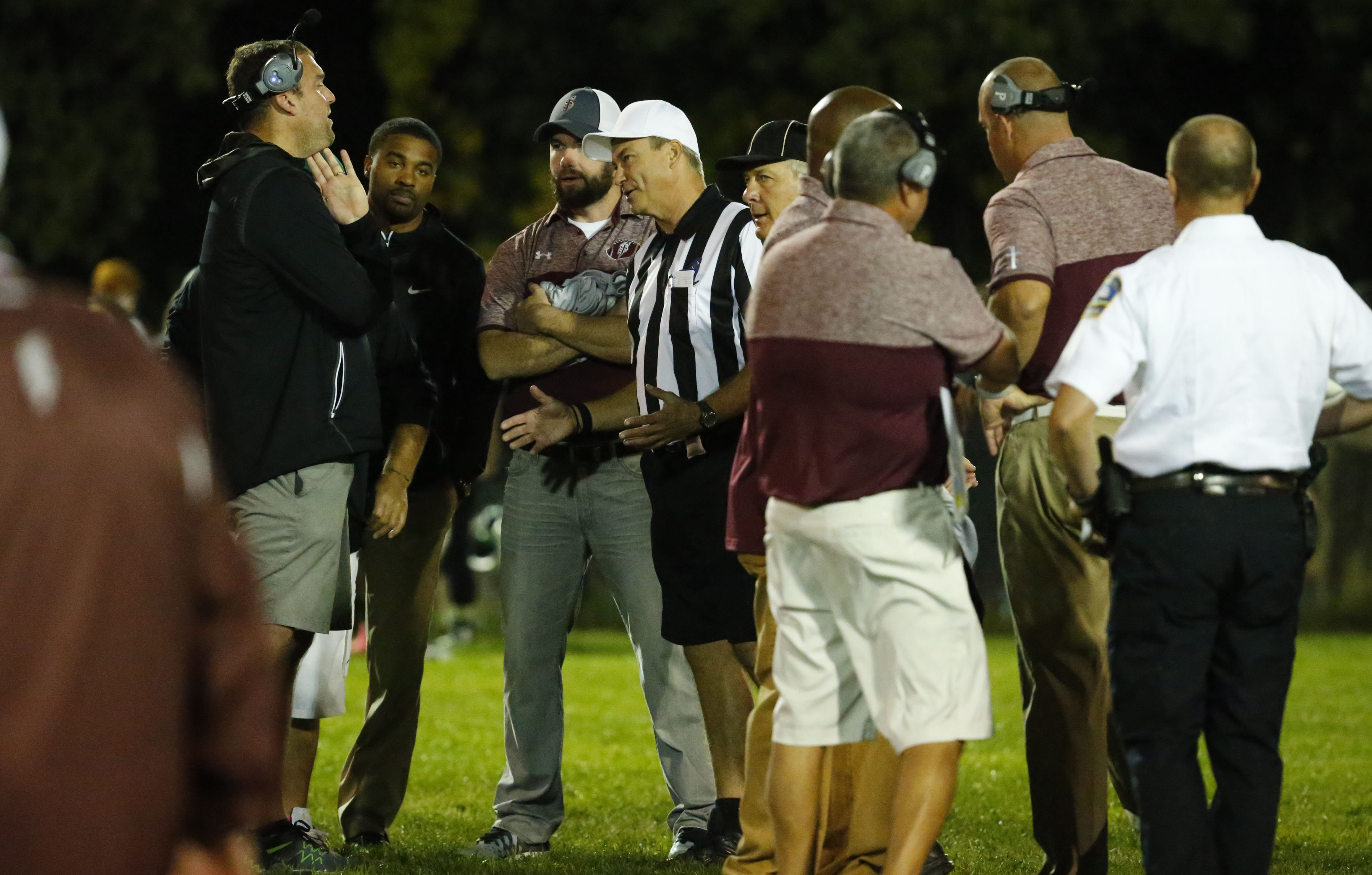 St. Joe's coach Derek Landri and Timon coach Charlie Comerford talk with officials while police look on after last Friday night's bench-clearing brawl. (Harry Scull Jr./Buffalo News)