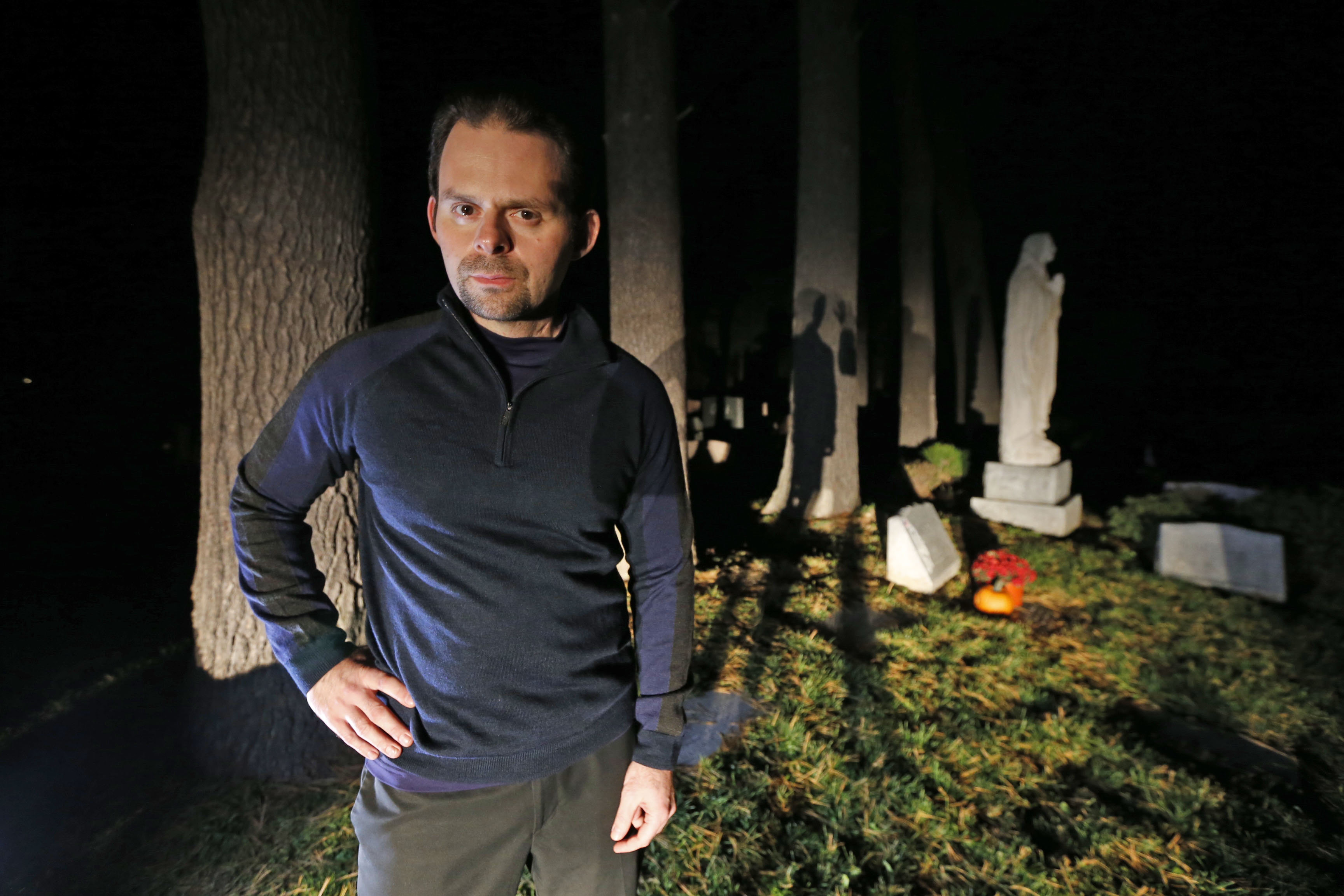 By day John Koerner teaches social science at ECC North. By night he is a student of the paranormal hunting for ghosts, speaking to the departed and giving walking tours in villages throughout the area.  This was in a cemetery in Hamburg on Monday, Oct. 10, 2016. (Robert Kirkham/Buffalo News)