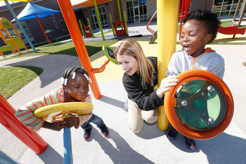 Lead teacher Jordan Beamer interacts with pre-schoolers from left, Cheyenne Stroudt, 4, and Elijah Henderson, 4, on the playground at the Children's Academy, 3149 Bailey Ave. in Buffalo on Wednesday, Oct. 12, 2016. (Robert Kirkham/Buffalo News)