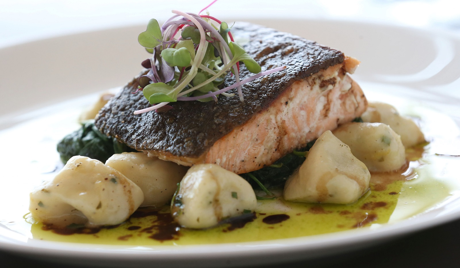 The crispy skin salmon from Panorama on Seven comes with potato gnocchi, spinach, chive oil and 25-year-old balsamic.  (Sharon Cantillon/Buffalo News)