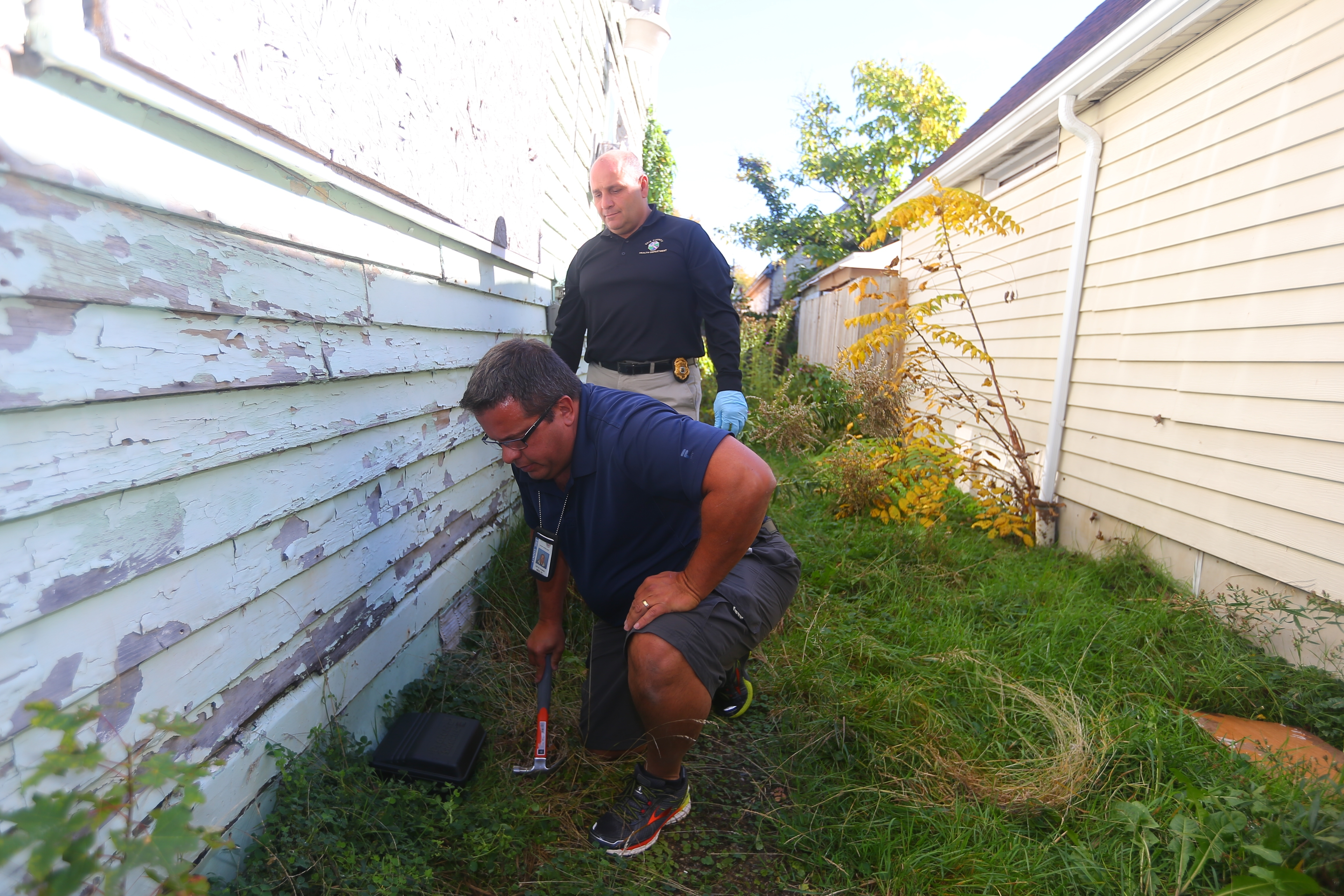 Guy Thomas, bottom, a Sr. Vector Control Investigator with the Erie County Vector Control program spikes a trap to the ground as Peter Tripi, Erie County Senior Public Helth Sanitation, looks on  at  a Cable Street house in Buffalo Wednesday.  (John Hickey/Buffalo News)
