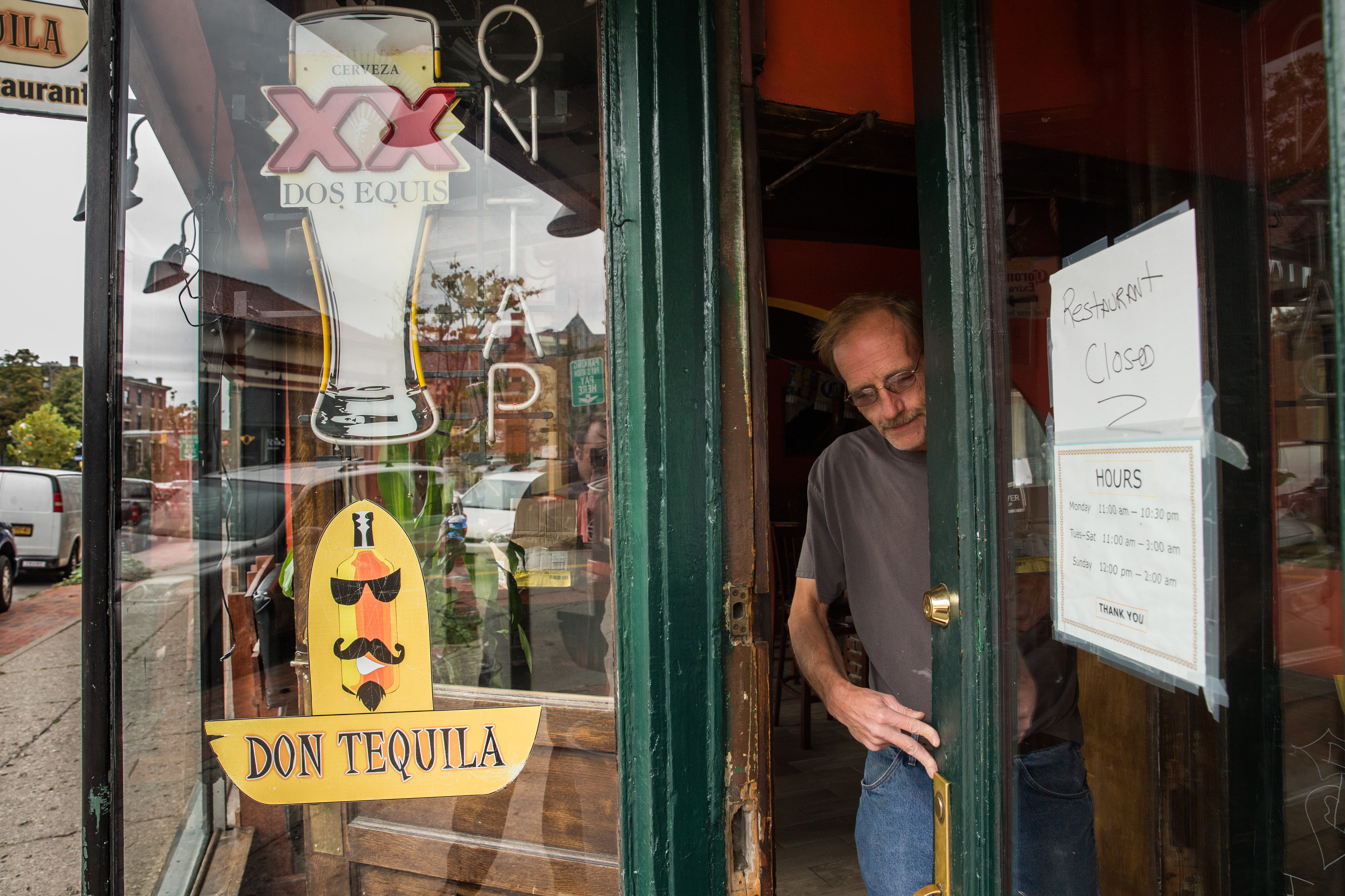 A representative of the building's owner changes the locks on the Don Tequila restaurant on Allen Street in Buffalo, which is closed following a law enforcement raid of the restaurant and several others for immigration issues, Tuesday, Oct. 18, 2016. (Derek Gee/Buffalo News)