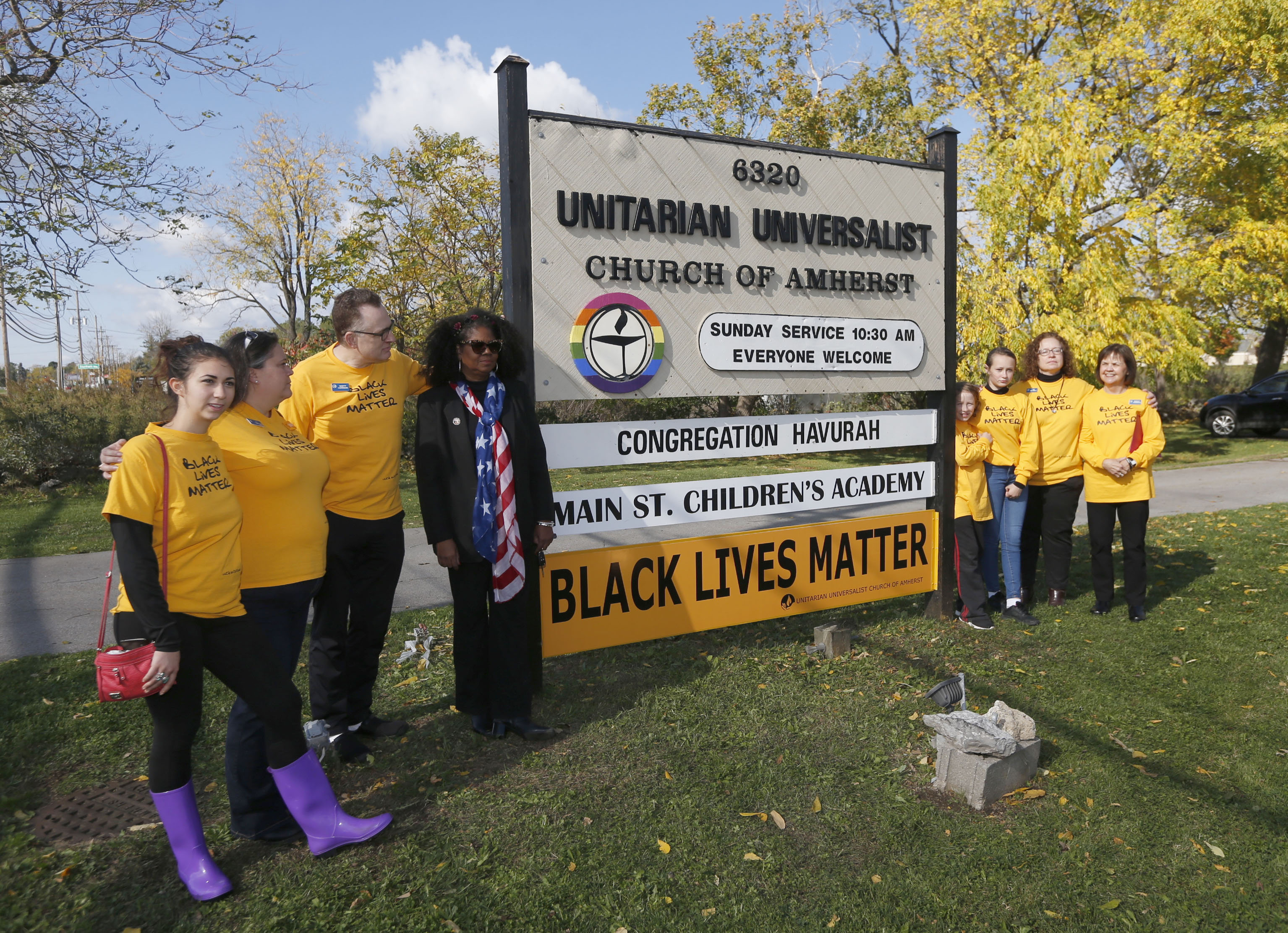 """Clergy and members of the Unitarian Universalist Church of Amherst took turns posing with the """"Black Lives matter"""" sign in front of said church on Main Street in Williamsville on Sunday, Oct. 23, 2016. (Robert Kirkham/Buffalo News)"""