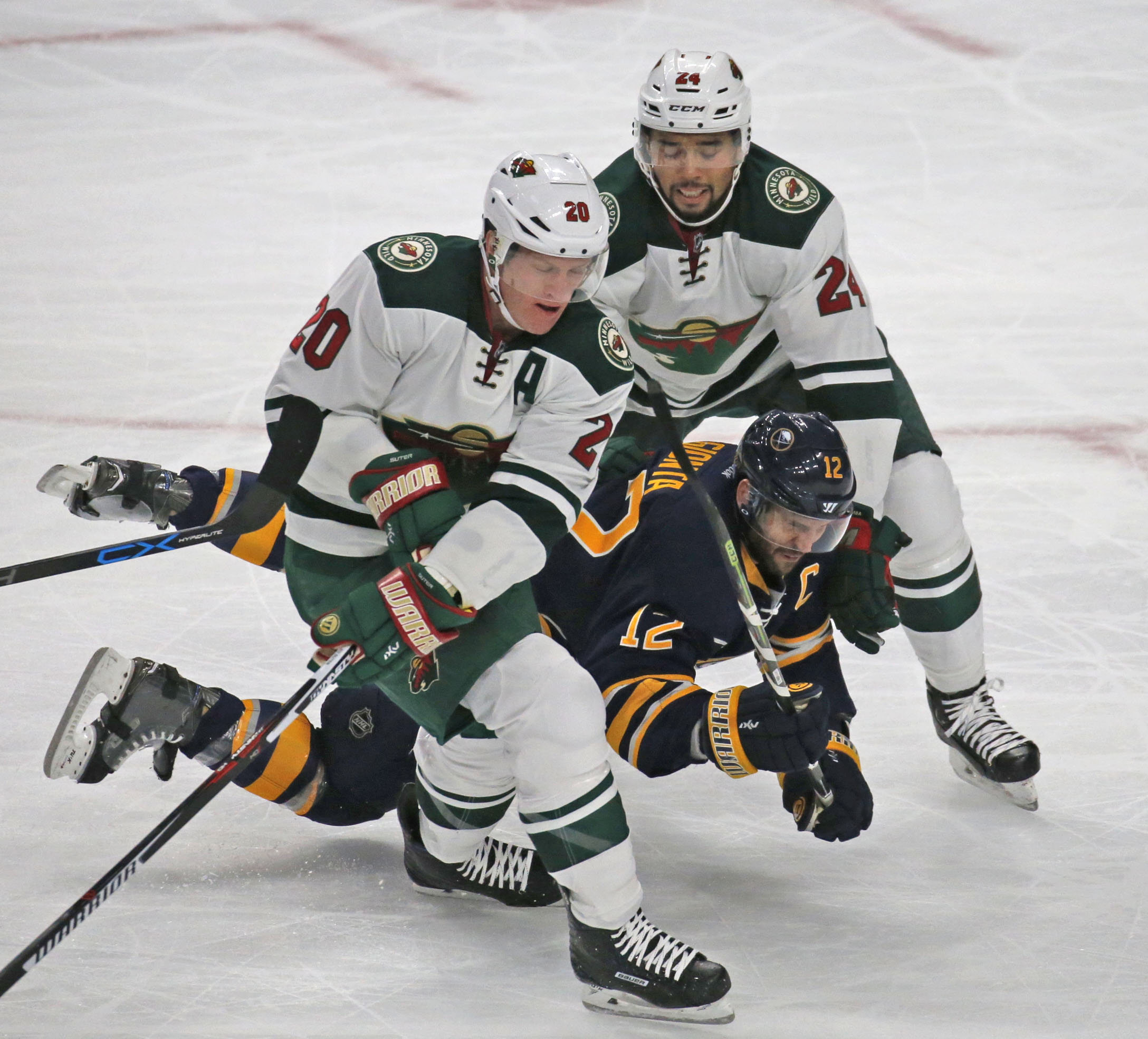 Buffalo's Brian Gionta (12) gets sandwiched by Minnesota defensemen Ryan Suter (20) and Matt Dumba (24) (Robert Kirkham/Buffalo News).