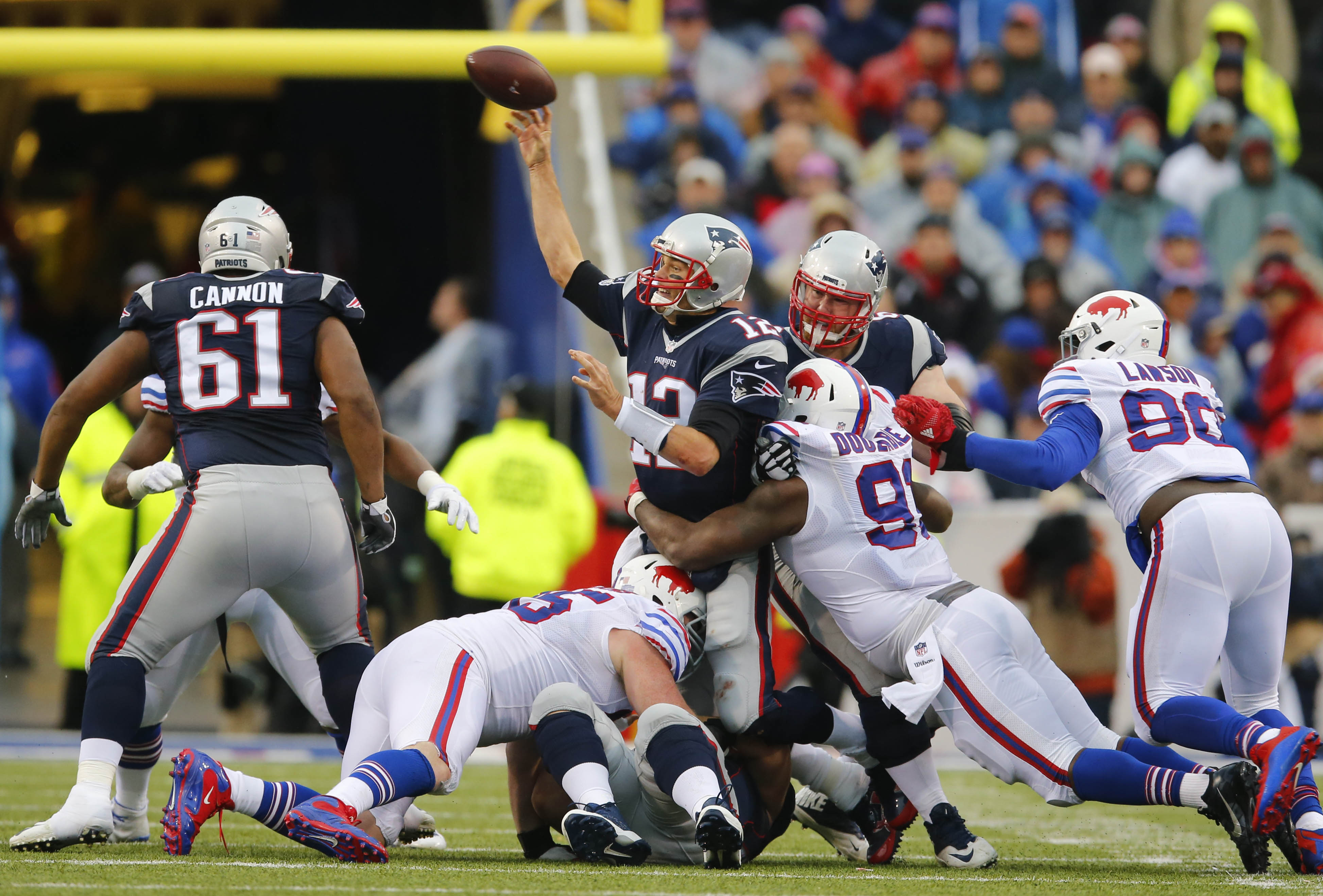 New England Patriots quarterback Tom Brady (12) throws the ball as he is hit by Buffalo Bills' Leger Douzable (91) during the second quarter. (Mark Mulville/Buffalo News)