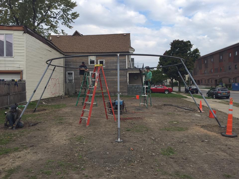 Workers install 'Full Circle,' a swingset and minimalist sculpture at 368 Auburn Ave. that is part of CEPA Gallery's West Side Lots public art project.