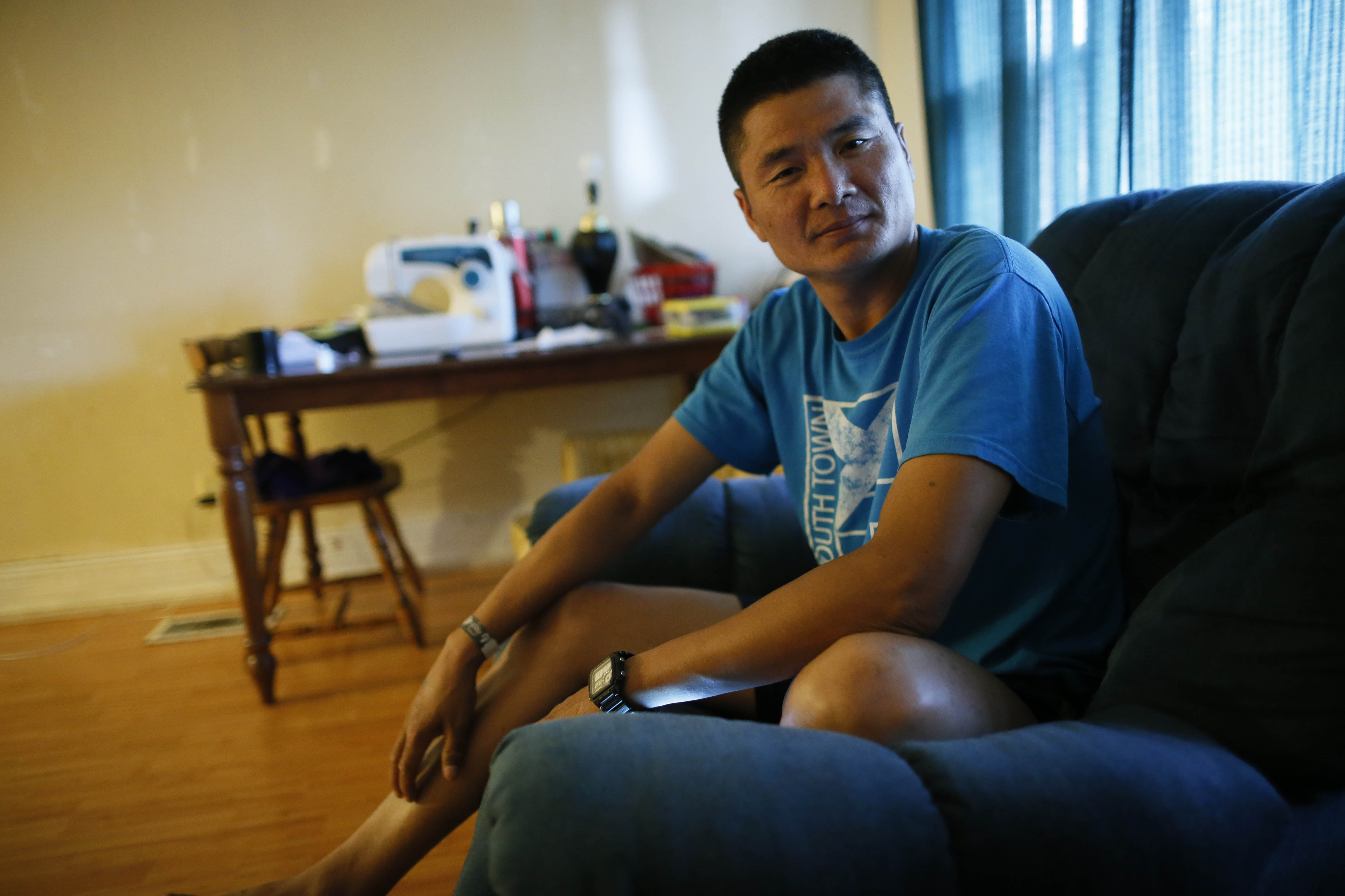 Nay Htoo, a Karen refugee who fled his home in the small village Kwee Ler Shu in Karen State, Myanmar, at a young age, relaxes in his Buffalo apartment Aug. 1. (Derek Gee/Buffalo News)