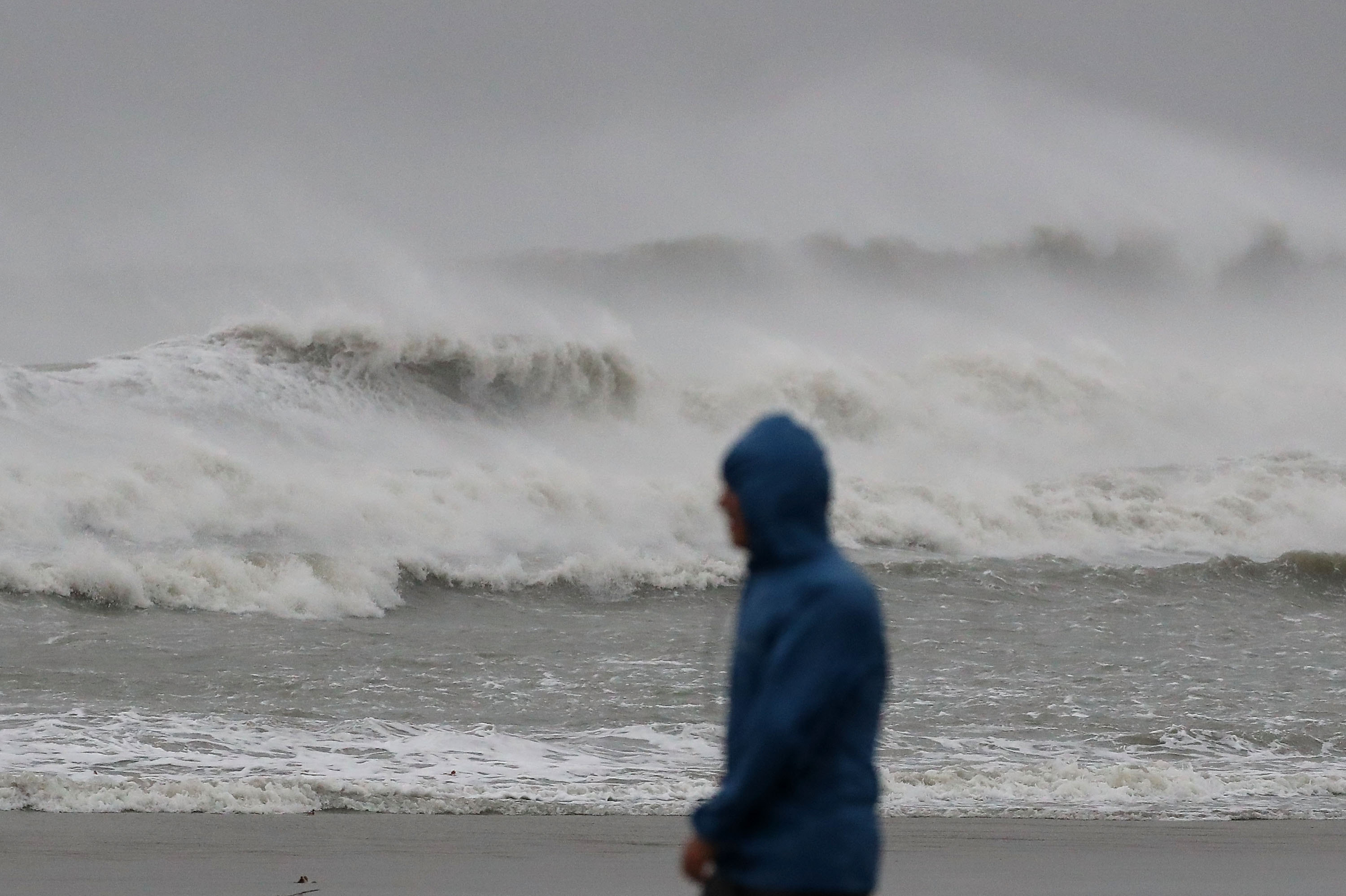 COCOA BEACH, FL - OCTOBER 07: A man walks past heavy surf caused by Hurricane Matthew, October 7, 2016 on Cocoa Beach, Florida. Hurricane Matthew passed by offshore as a catagory 3 hurricane bringing heavy winds and minor flooding. (Photo by Mark Wilson/Getty Images)