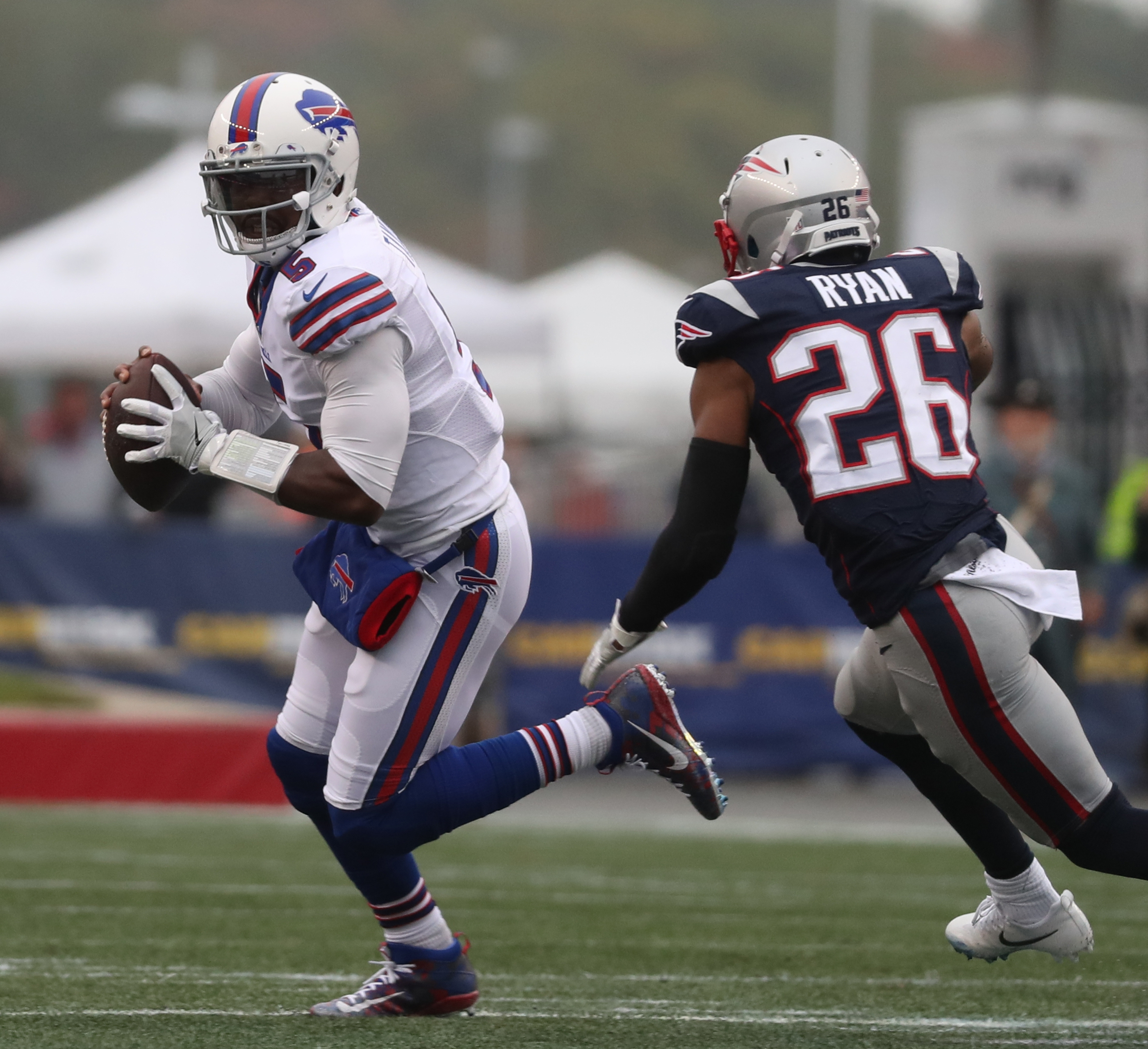 Buffalo Bills quarterback Tyrod Taylor (5) avoids a sack by New England Patriots cornerback Logan Ryan (26) in the first quarter.