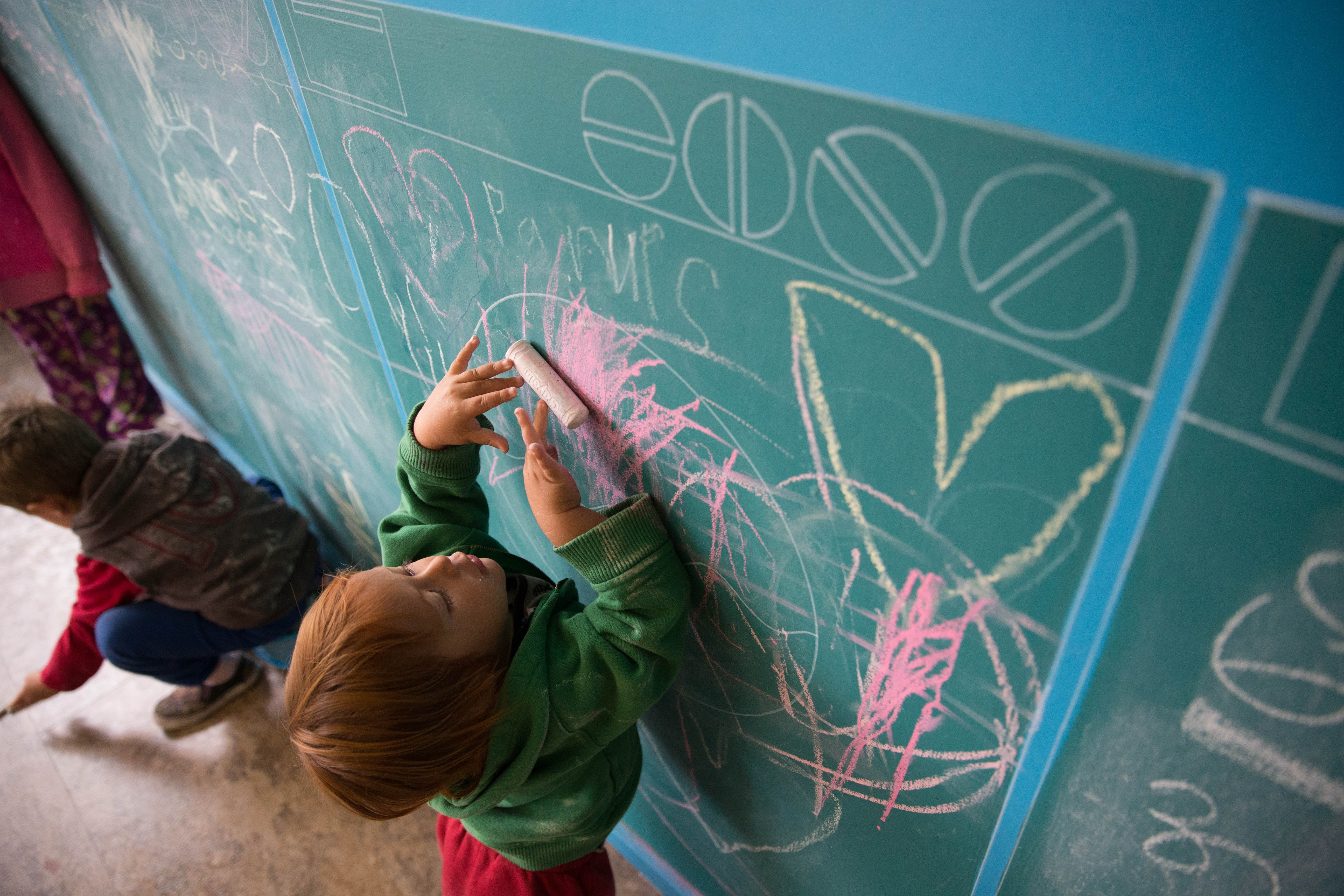 Hugo Bradley, 1, colors on the chalk wall Friday during the grand opening of the WASH Project at its new, temporary location on Grant Street. The program's former location on Massachusetts Avenue will be rehabbed by PUSH Buffalo over the next two years.