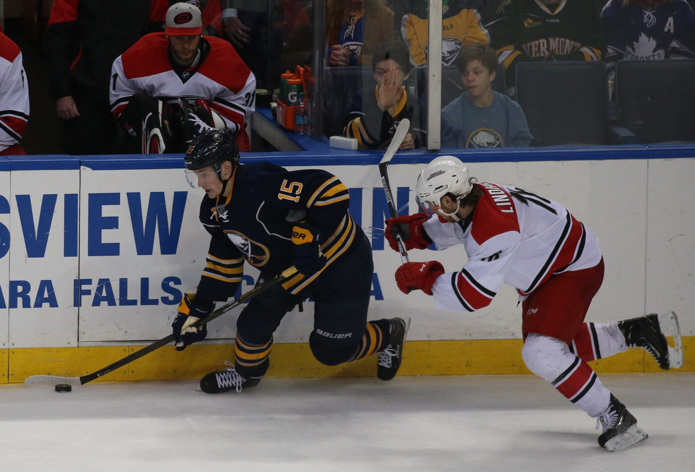 Buffalo Sabres' Jack Eichel (15) brings the puck up the boards as  Carolina Hurricanes' Elias Lindholm (16) checks from behind in third period action at  First Niagara Center, Buffalo, N.Y., on  Saturday,  March 12, 2016.Sabres 3, Hurricanes 2, in overtime session of play. (John Hickey/Buffalo News)