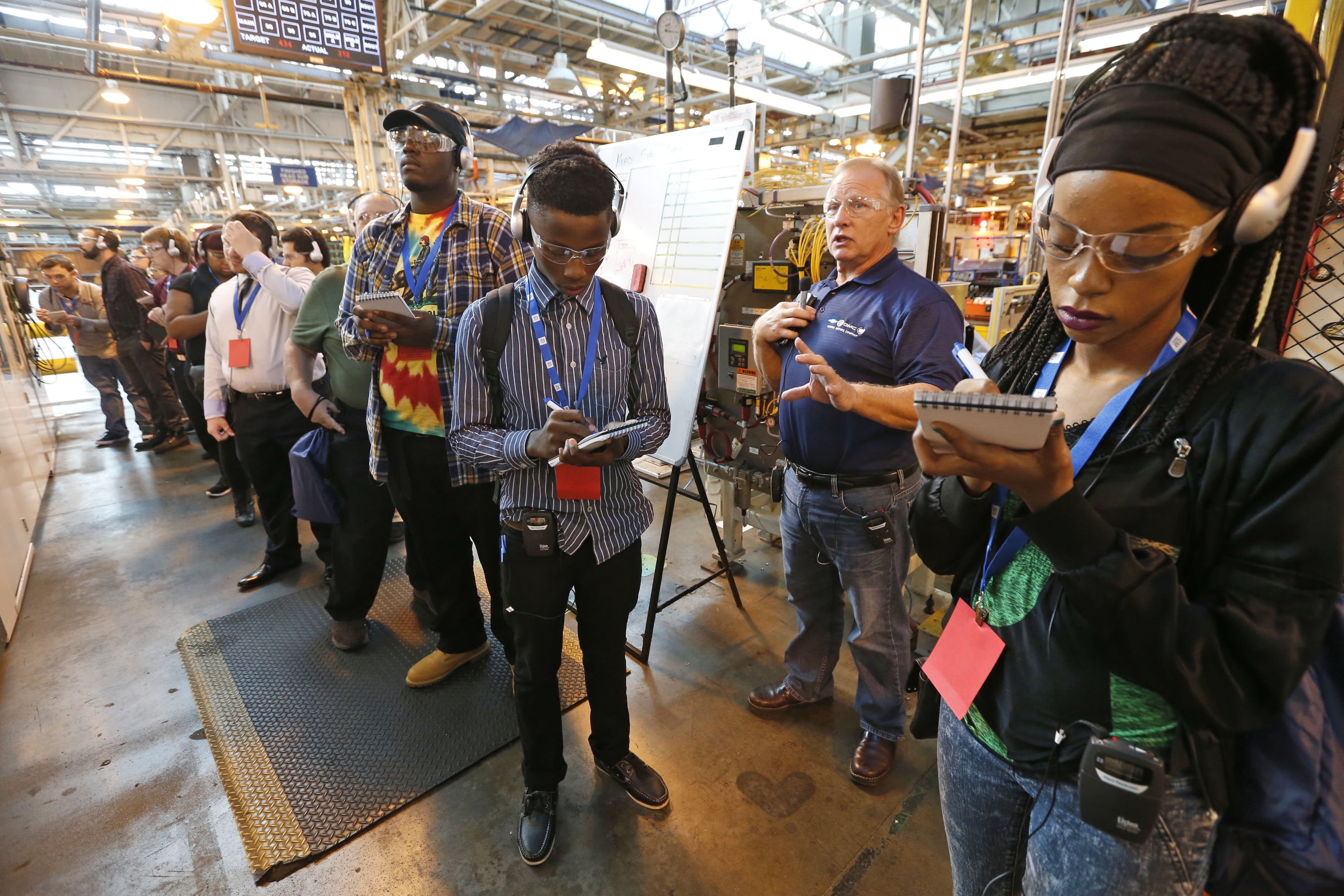 """Mike Knop, a General Motors retiree, leads a group of about 100 local high school students and teachers on a tour of GM's engine plant in the Town of Tonawanda on Wednesday. One point of interest was a robotic unit that he called """"a one-of-a-kind system in the world."""""""