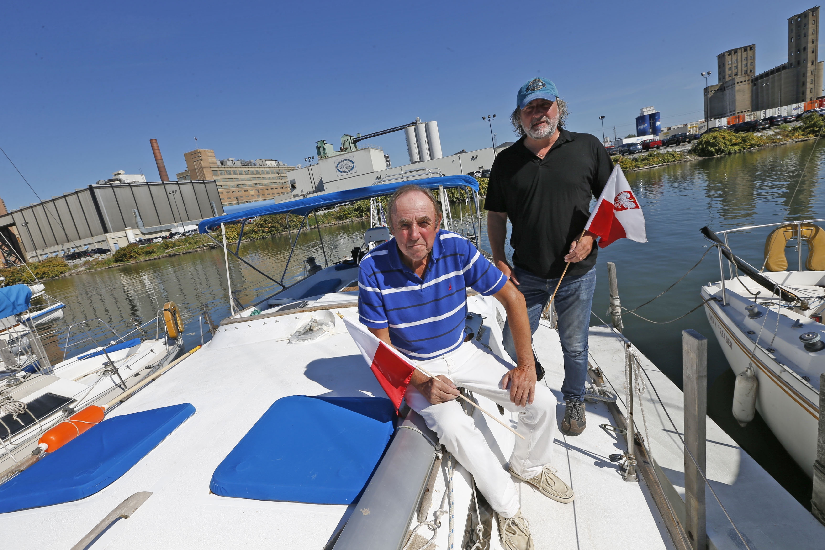 Capt. Andrew W. Piotrowski, left, with documentarian Peter Rudzinski, hold Polish flags near their boat at RCR Yacht's marina in Buffalo on Wednesday, Oct. 5, 2016. (Robert Kirkham/Buffalo News)