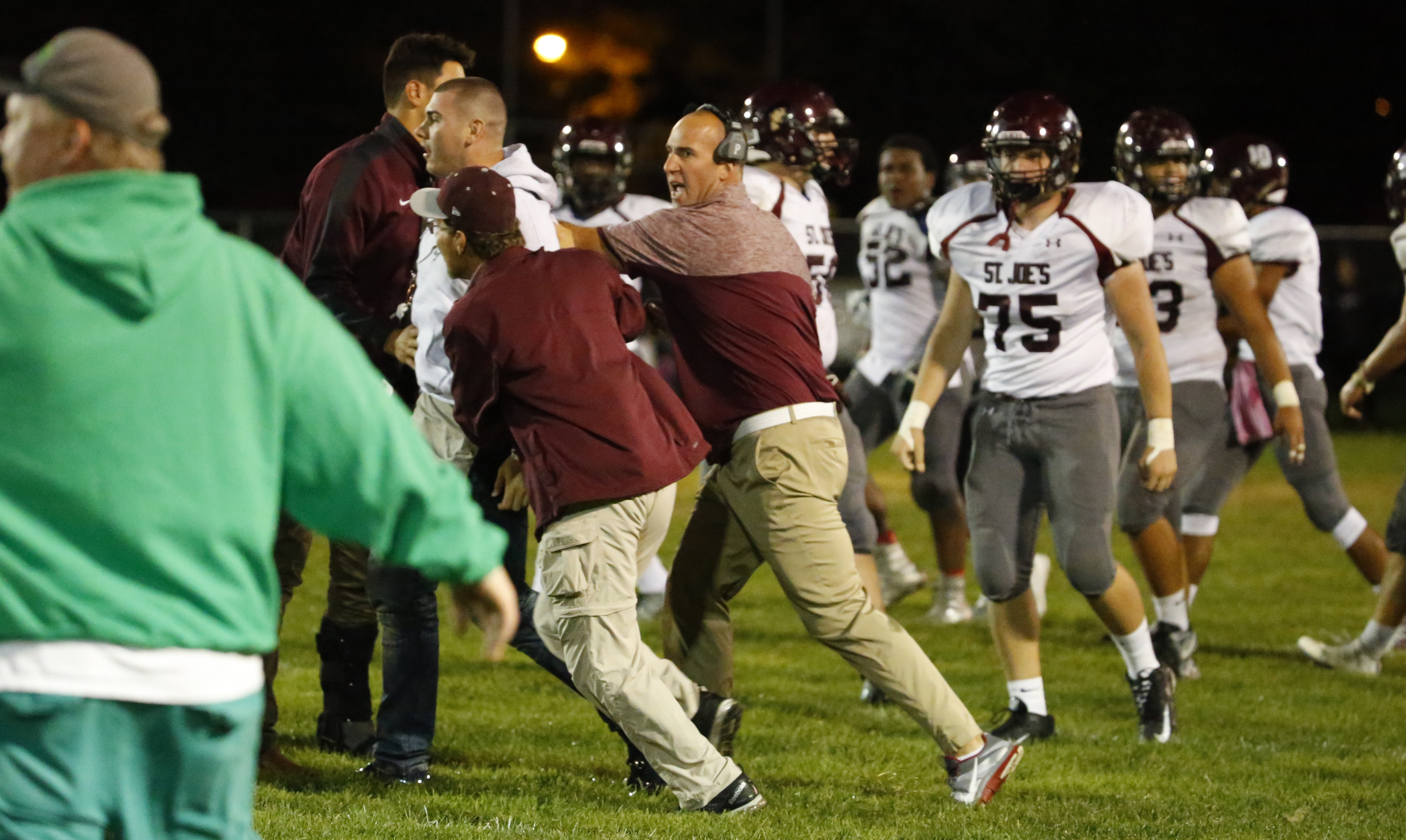 St. Joe's alumni and Ole Missippi quarterback Chad Kelly is restrained after leaving the stand to come to the aid of his brother Casey who was involved in and altercation with the Timon bench during second quarter action at Tiff farms on Friday,Oct. 7, 2016.(Harry Scull Jr./Buffalo News)