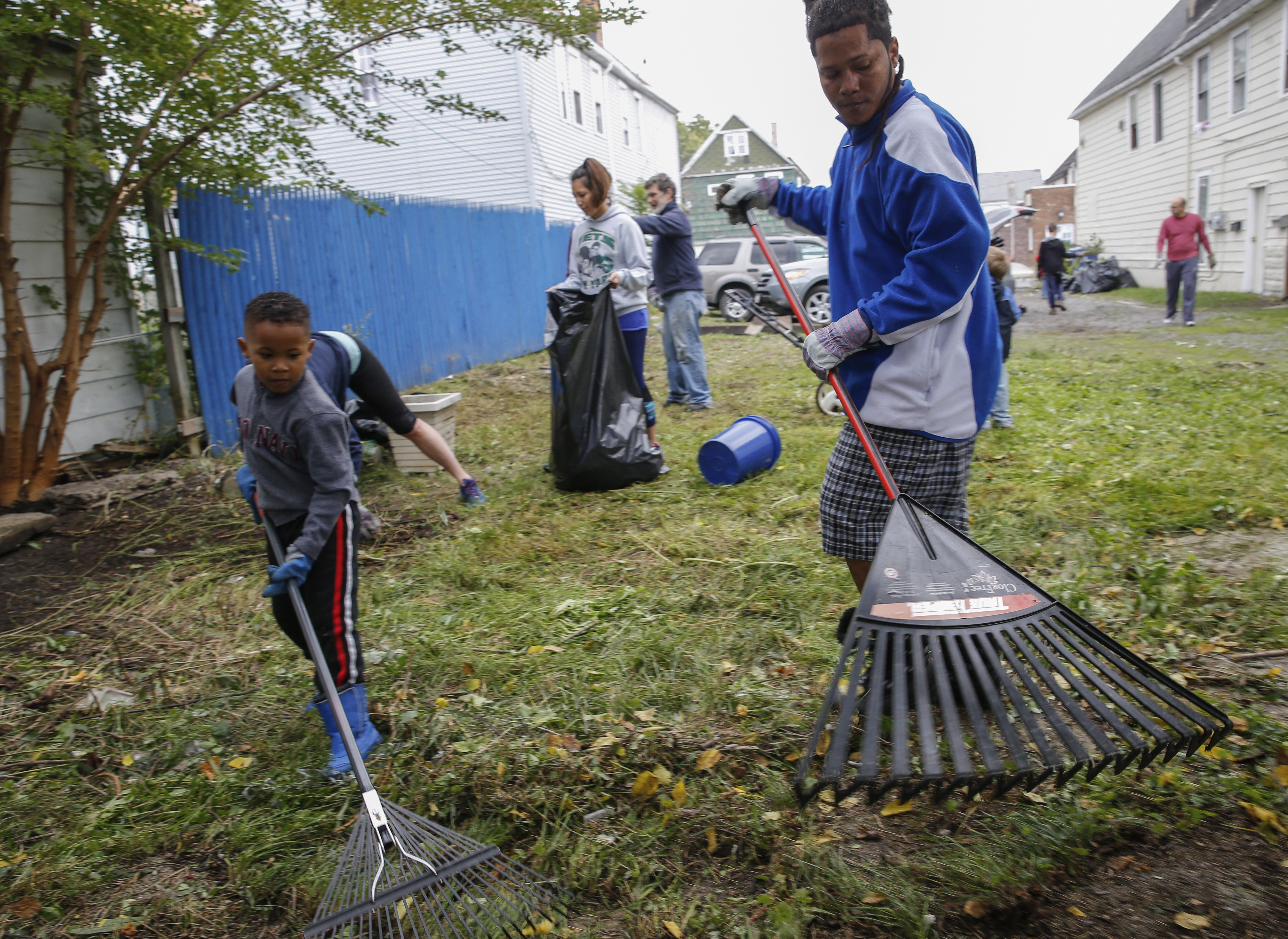 Diego Alexander, right, a refugee from Colombia, and his son Joel Sebastian, 6, rake up debris in a Bailey Avenue yard Sunday. They joined  volunteers from Congregation Shir Shalom and the Boy Scouts to help Jewish Family Service clean up the lot next to an apartment building where four refugee families live.