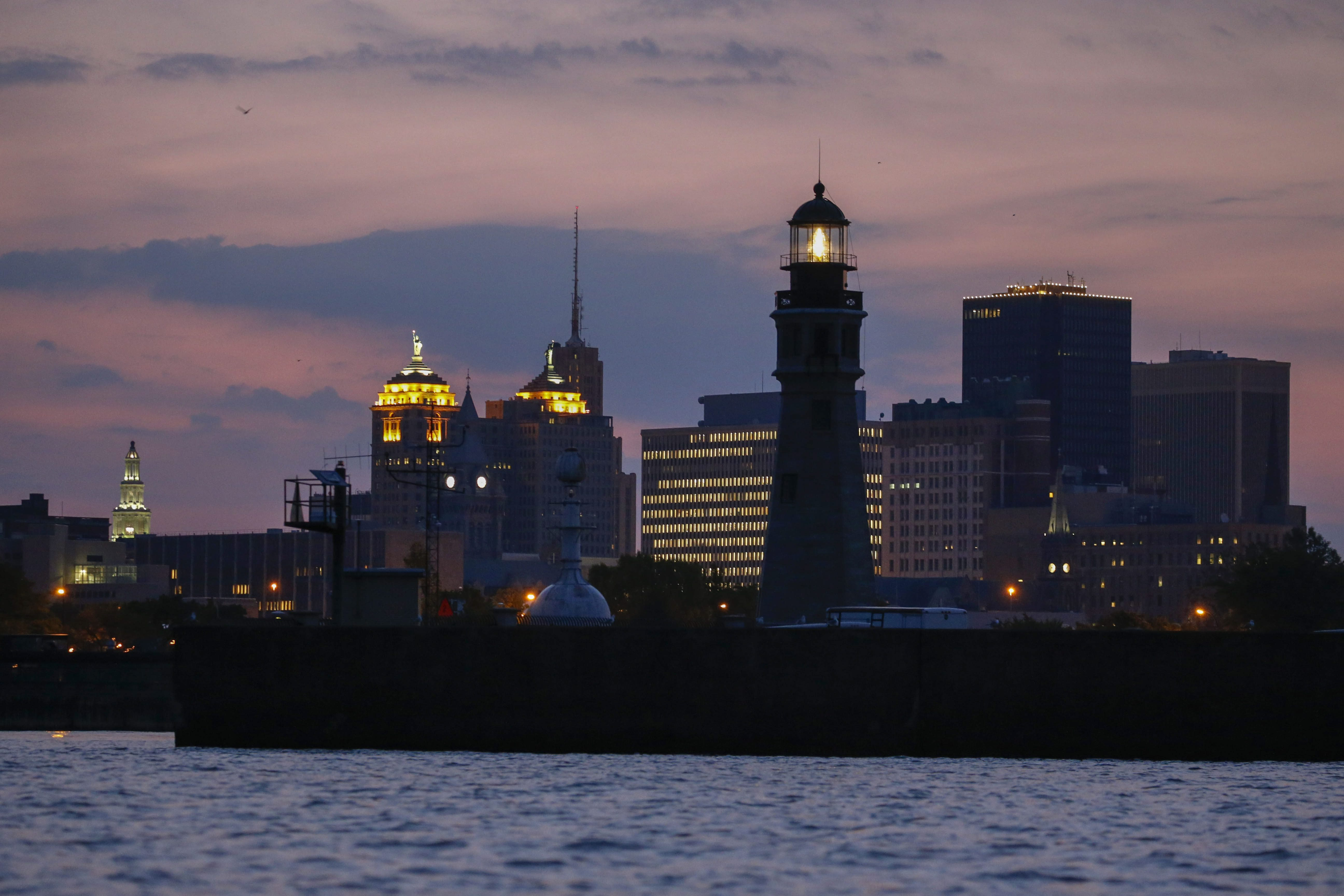 The Buffalo Lighthouse shines before daybreak, Wednesday, July 6, 2016.  A new acrylic and brass fresnel lens was recently installed to bring light back to the entrance of the Buffalo River.  (Photo by Derek Gee)