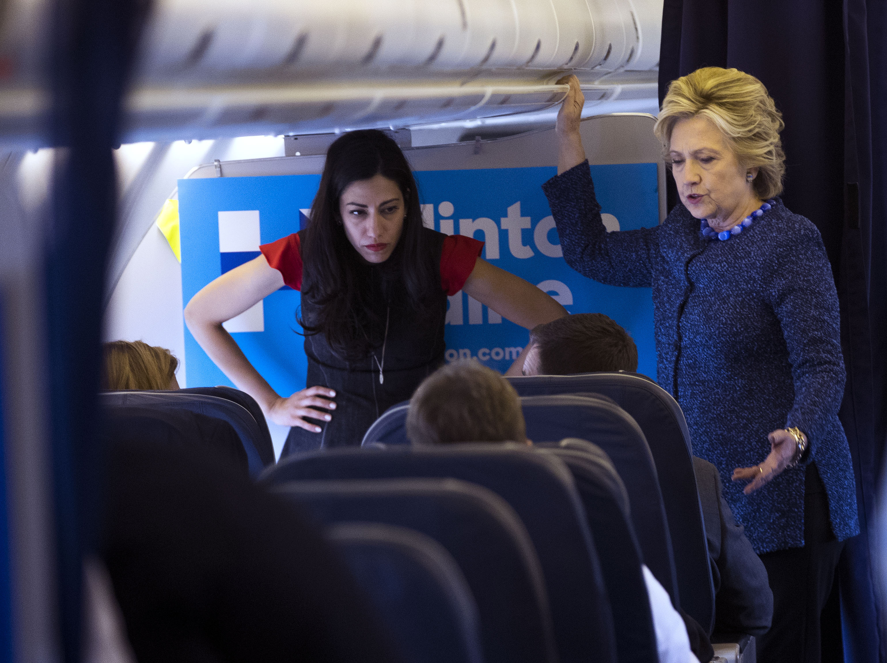 Hillary Clinton with aide Huma Abedin, right, aboard Clinton's campaign plane as they head to Cedar Rapids, Iowa, for a campaign rally, Friday, Oct. 28, 2016. Federal law enforcement officials said Friday that the new emails uncovered in the closed investigation into Clinton's use of a private email server were discovered after the FBI seized electronic devices belonging to Abedin and her husband, Anthony Weiner. (Doug Mills/The New York Times)