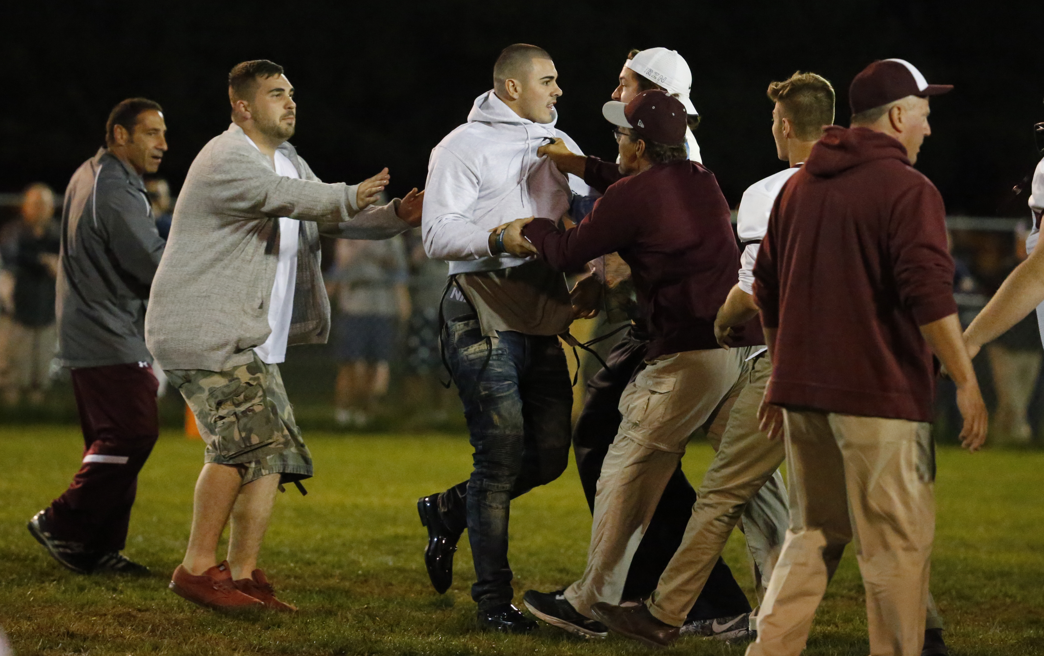 Chad Kelly was held back after running onto the field during the fight. (Harry Scull Jr./Buffalo News)