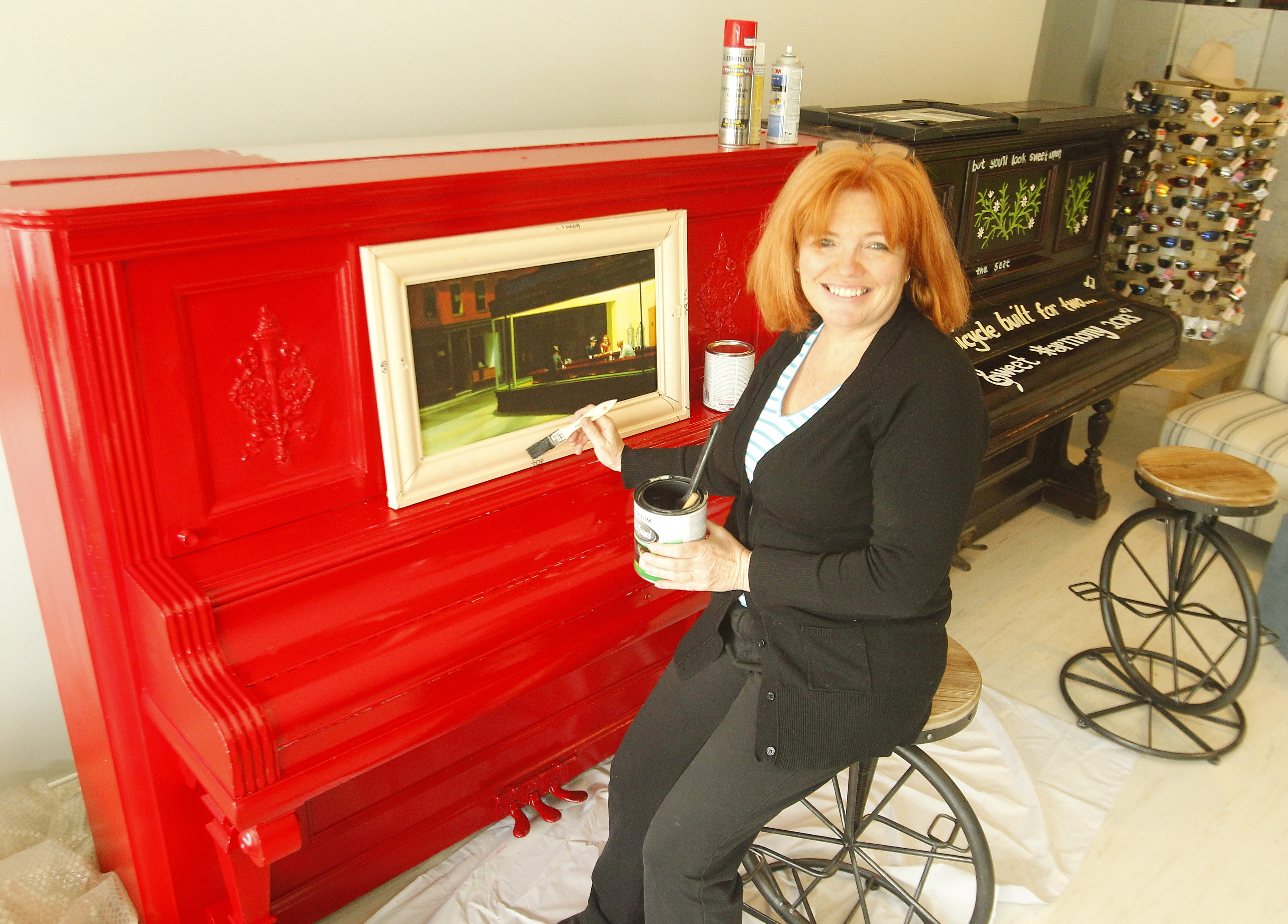 Ellen Martin launched a public art project in Lockport, N.Y., in 2013 that  placed used painted pianos in front of businesses for people to admire or play. Martin posed with two of the pianos in Lockport on  Tuesday, May 14, 2013.  (John Hickey/Buffalo News)