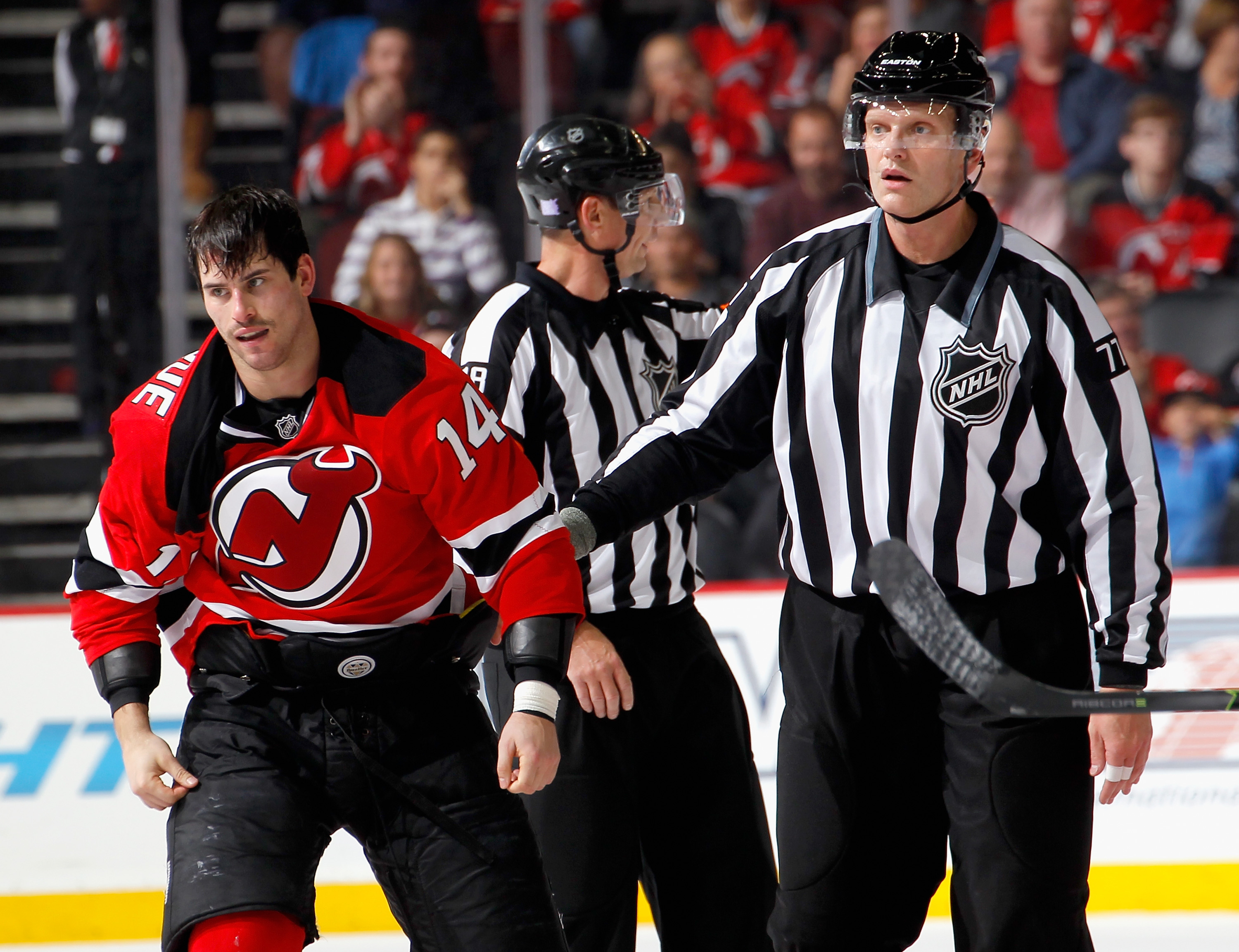 NEWARK, NJ - NOVEMBER 06: Adam Henrique #14 of the New Jersey Devils is escorted off the ice by linesman Tim Nowak #77 after fighting with Jonathan Toews of the Chicago Blackhawks during an NHL hockey game at Prudential Center on November 6, 2015 in Newark, New Jersey. (Photo by Paul Bereswill/Getty Images)