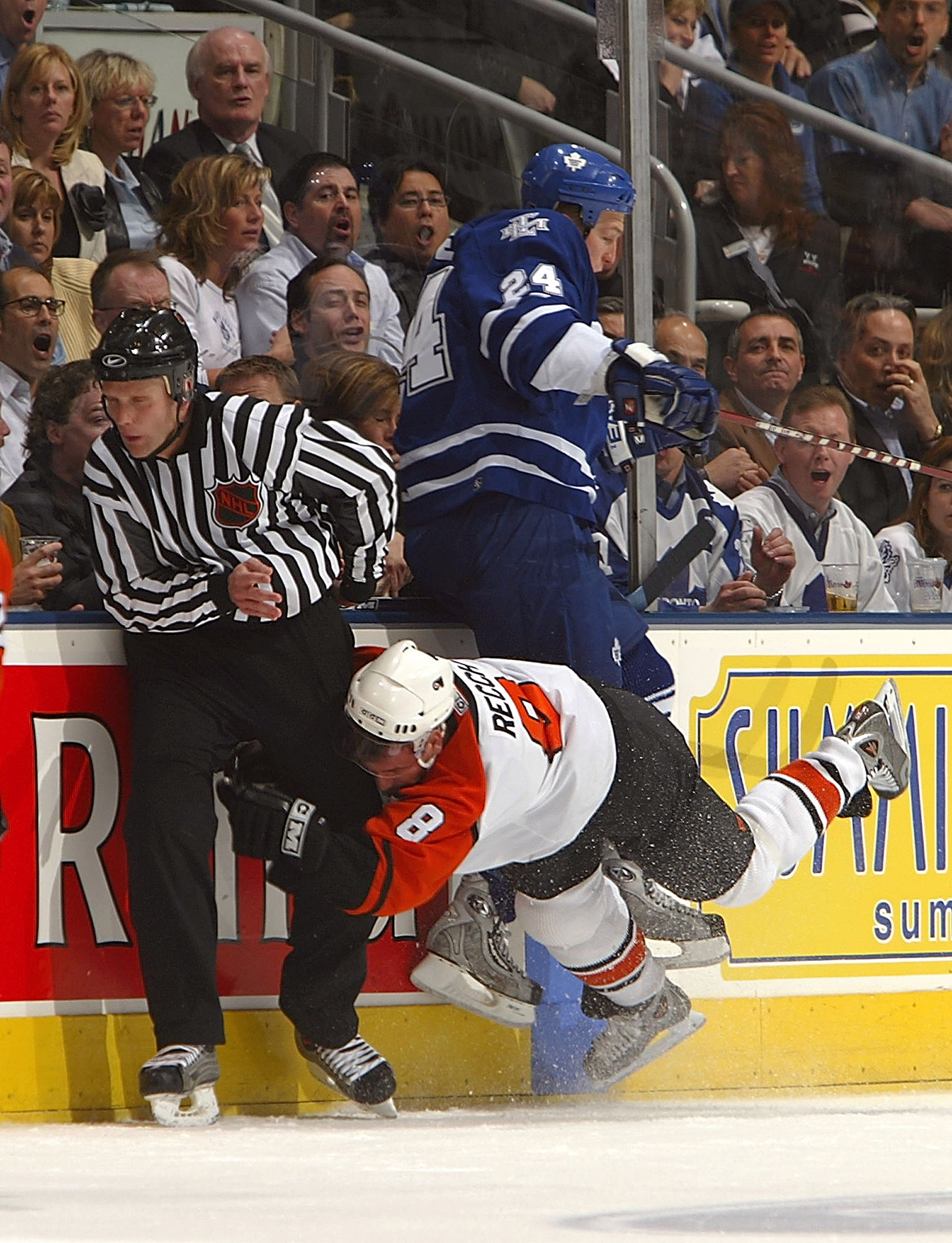 TORONTO - APRIL 28: Mark Recchi #8 of the Philadelphia Flyers and linesman Tim Nowak are both taken out on a check from Bryan McCabe #24 of the Toronto Maple Leafs in Game three of the Eastern Conference Semifinals during the 2004 NHL Stanley Cup Playoffs April 28, 2004 at Air Canada Centre in Toronto, Ontario, Canada. (Photo by Dave Sandford/Getty Images)