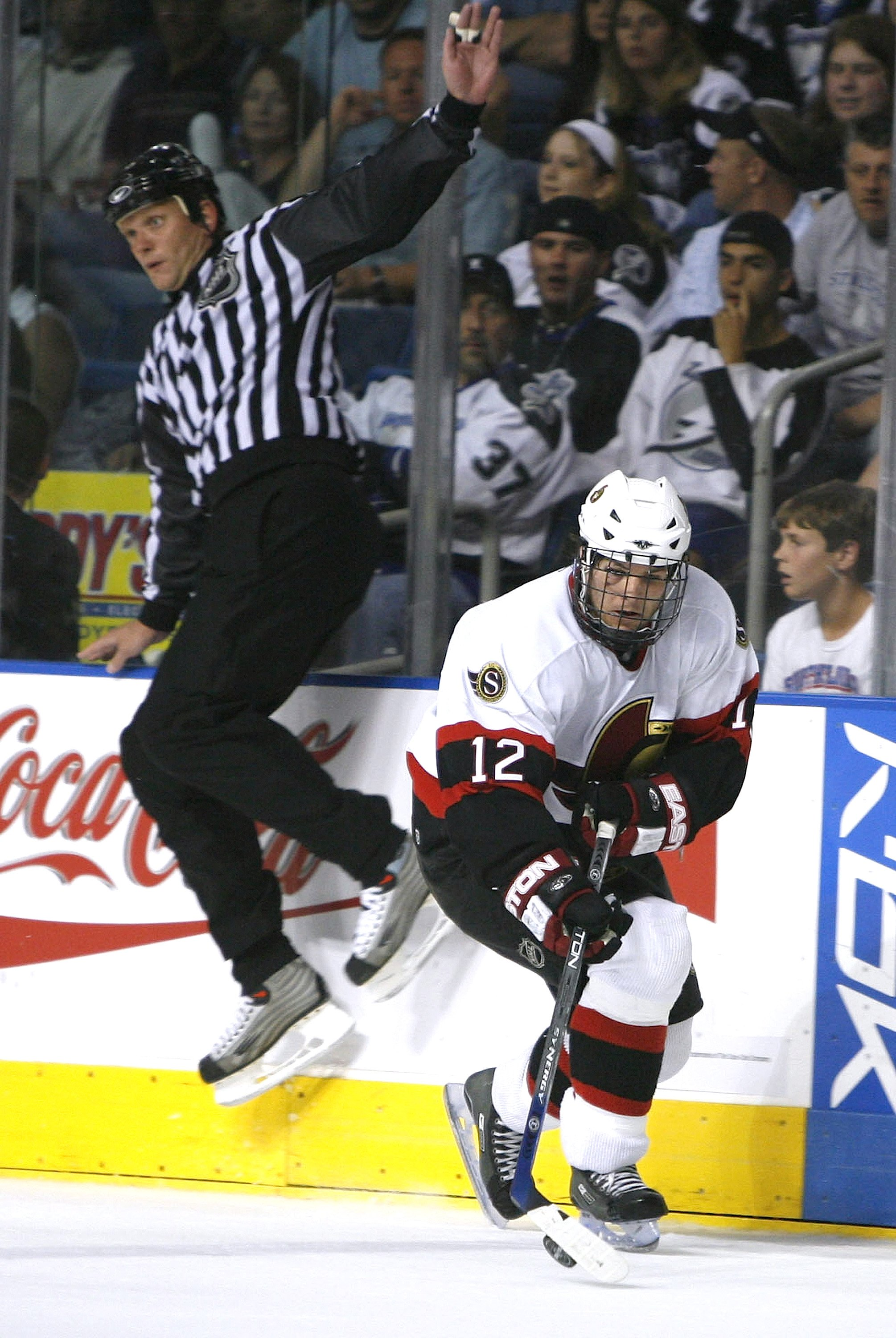 TAMPA, FL - APRIL 27: Linesmen Tim Nowak jumps out of the way of Mike Fisher #12 of the Ottawa Senators as he skates down ice against the Tampa Bay Lightning in the third period during game four round one of the Eastern Conference 2006 NHL Stanley Cup Playoffs at the St. Pete Times Forum on April 27, 2006 in Tampa, Florida. (Photo by Eliot J. Schechter/Getty Images)