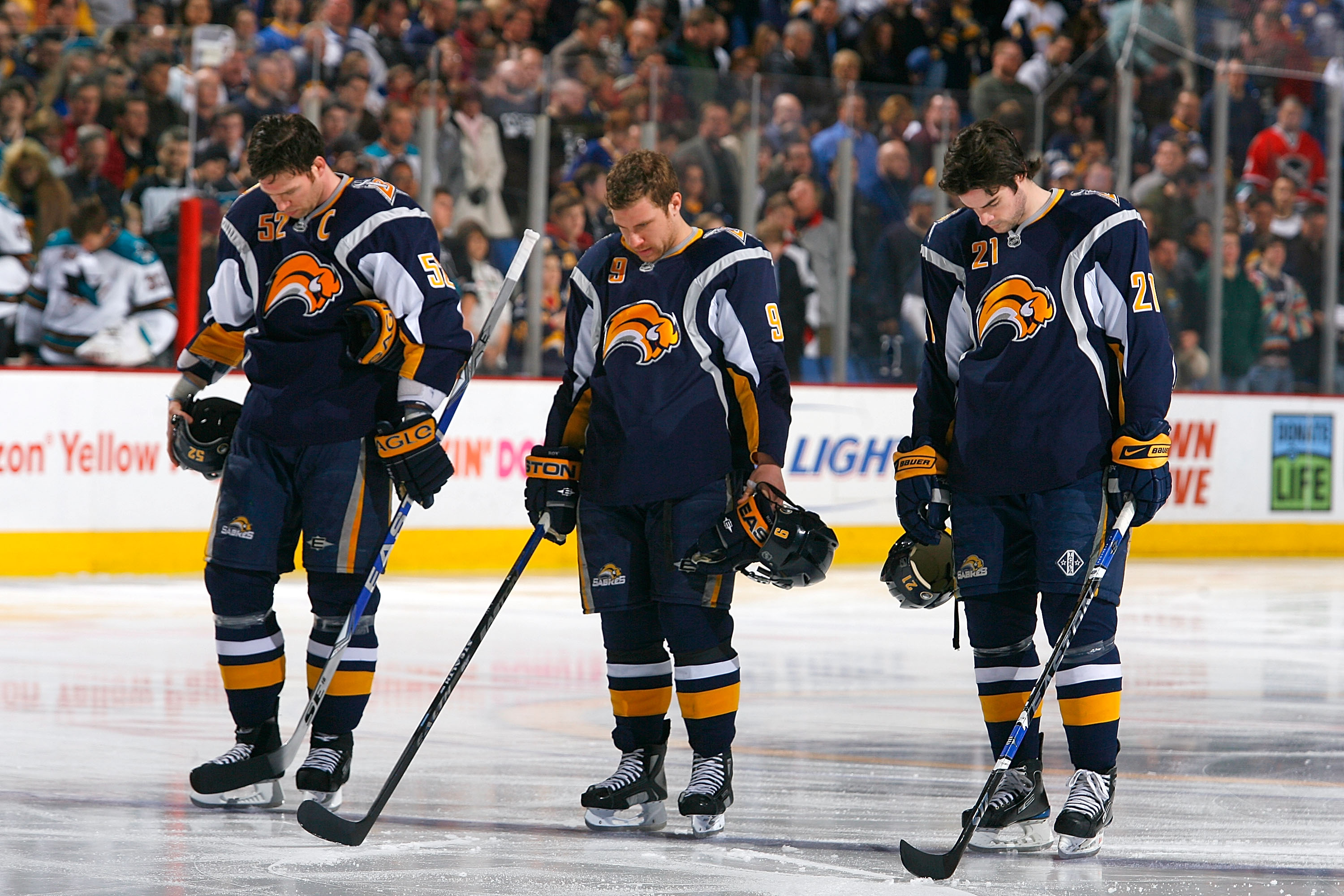 BUFFALO, NY - FEBRUARY 13: Craig Rivet #52, Derek Roy #9 and Drew Stafford #21 of the Buffalo Sabres pause for a moment of silence for the victims of Continental Connection flight 3407 prior to playing the San Jose Sharks on February 13, 2009 at HSBC Arena in Buffalo, New York. The flight crashed in the Buffalo suburb of Clarence Center on Feb 12, 2009. (Photo by Rick Stewart/Getty Images)