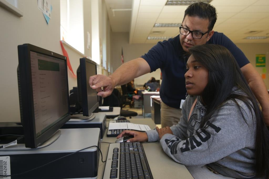 Roberto Bonilla, a youth advocate with Hillside Work-Scholarship Connection helps Kevianys Sanchez, 16, a 10th-grader at South Park High School, on Oct. 12. (John Hickey/Buffalo News)