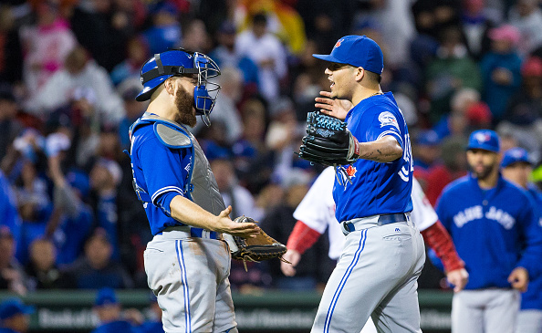 Blue Jays closer Roberto Osuna and catcher Russell Martin celebrate the final out Saturday in Fenway Park -- a scene they hope to repeat today (Getty Images).