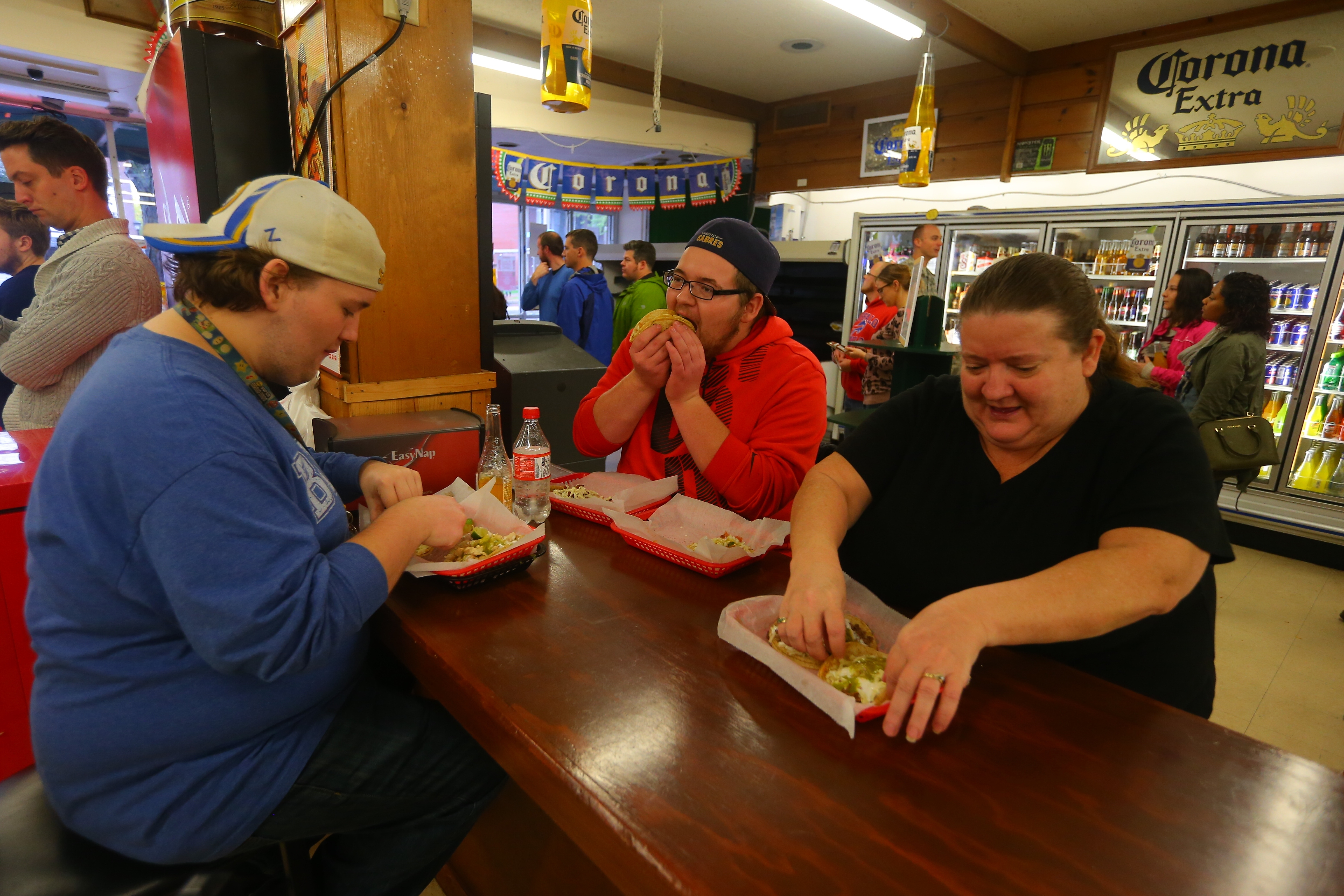 Jack Ceder, left, and his brother Cody Ceder, take their mother Debbie Green out for a taco lunch at La Divina Mexican Store on Friday Oct. 21, 2016, La Divina Mexican Store reopened after briefly closing following a raid by federal agents and the arrest of owner Sergio Mucino and several employees, in Kenmore, N.Y., earlier this week. (John Hickey/Buffalo News)