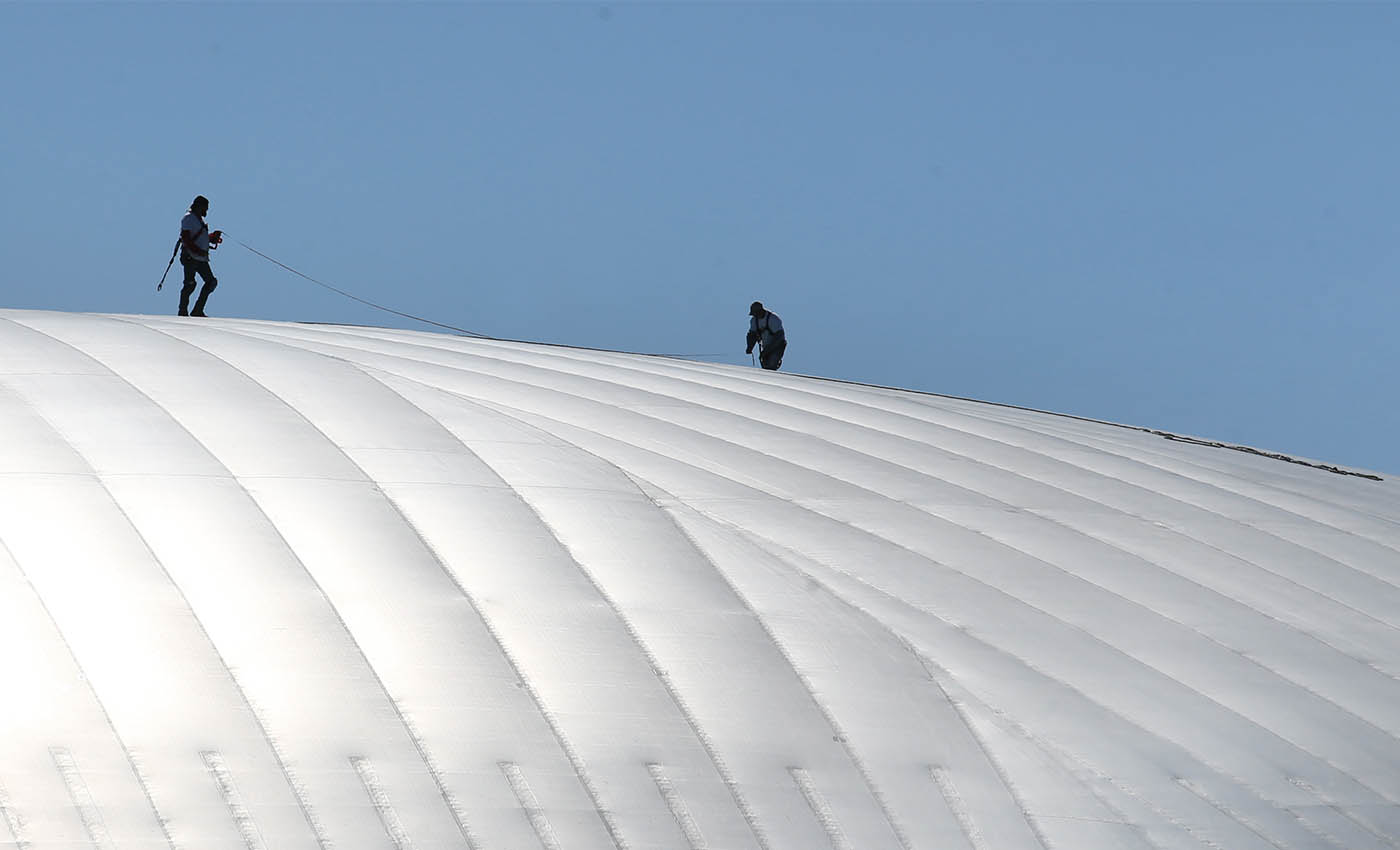 Two men do some work atop of the KeyBank Center, Friday, Oct. 14, 2016. (Sharon Cantillon/Buffalo News)