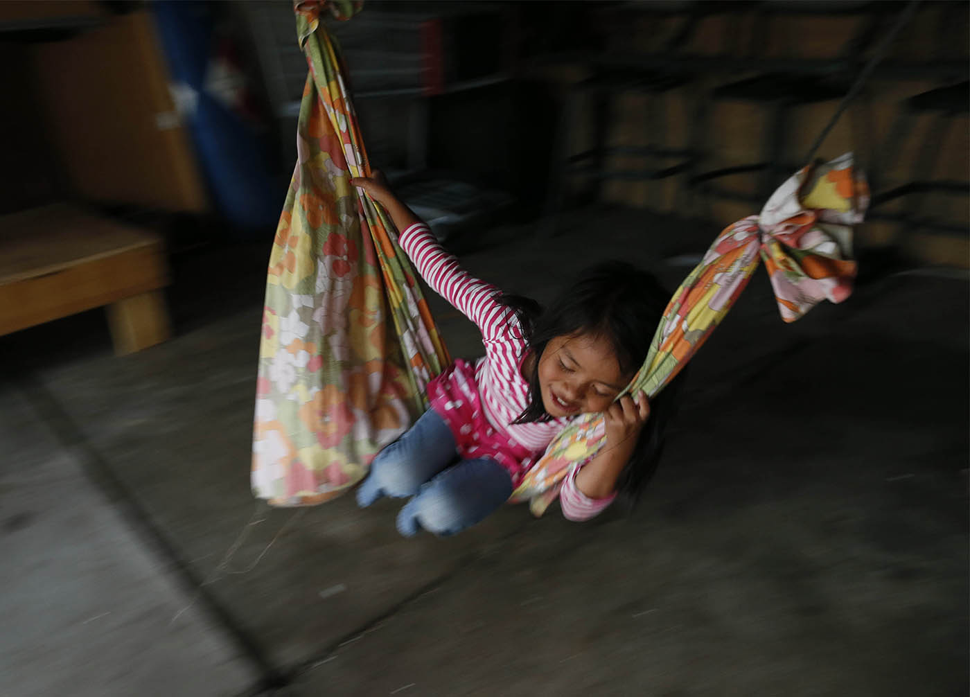 Naomi Tay, 5, plays in a makeshift hammock in the garage of a relative in Riverside, Wednesday, Aug. 12, 2015. (Derek Gee/Buffalo News)
