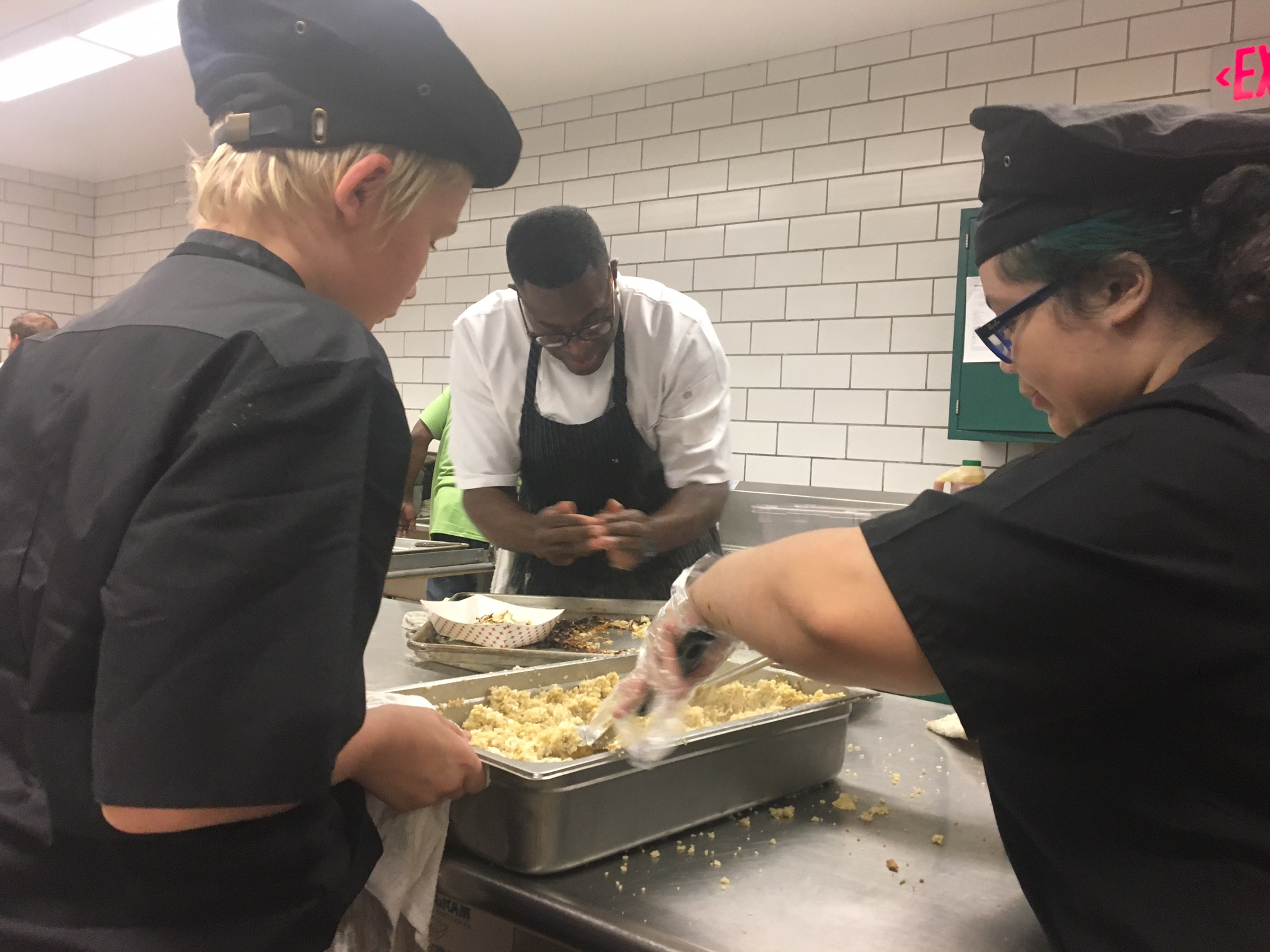 Southside Elementary eighth-graders Quinn Colin, left, and Raven Littlejohn, right, flank chef Bobby Anderson as they work on Anderson competition entry in the Southside kitchen.
